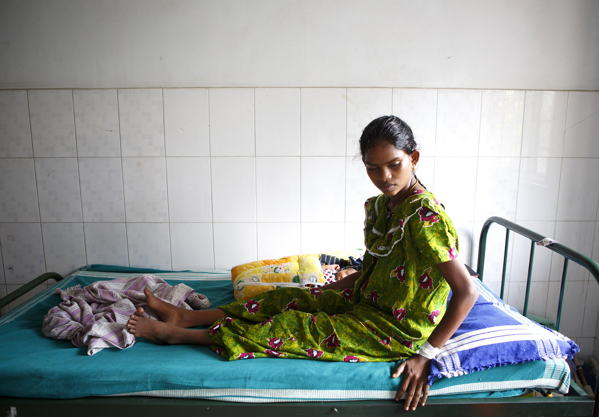 A mother, with her infant beside her, at the Medavakkam Primary Health Centre in Tamil Nadu in December, 2014.  SARAH WEISER