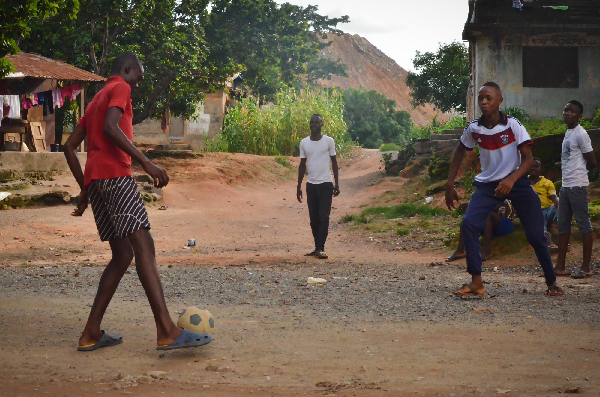 "While waiting for the bi-weekly mine blasting to end, young men pass time by playing football at a security checkpoint. Their homes are within the mine's 500-meter ""safety zone,"" which makes them vulnerable to flying debris."