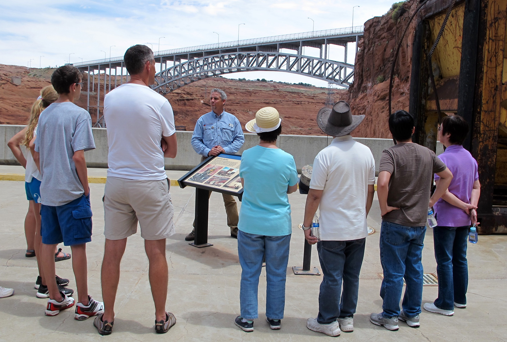 A tour group stands at Glen Canyon Dam, the head of Lake Powell. The dam and the lake it created are at the center of a $250 million dollar tourism industry in Page, Arizona. (Photo by Charlotte Weiner/GroundTruth)