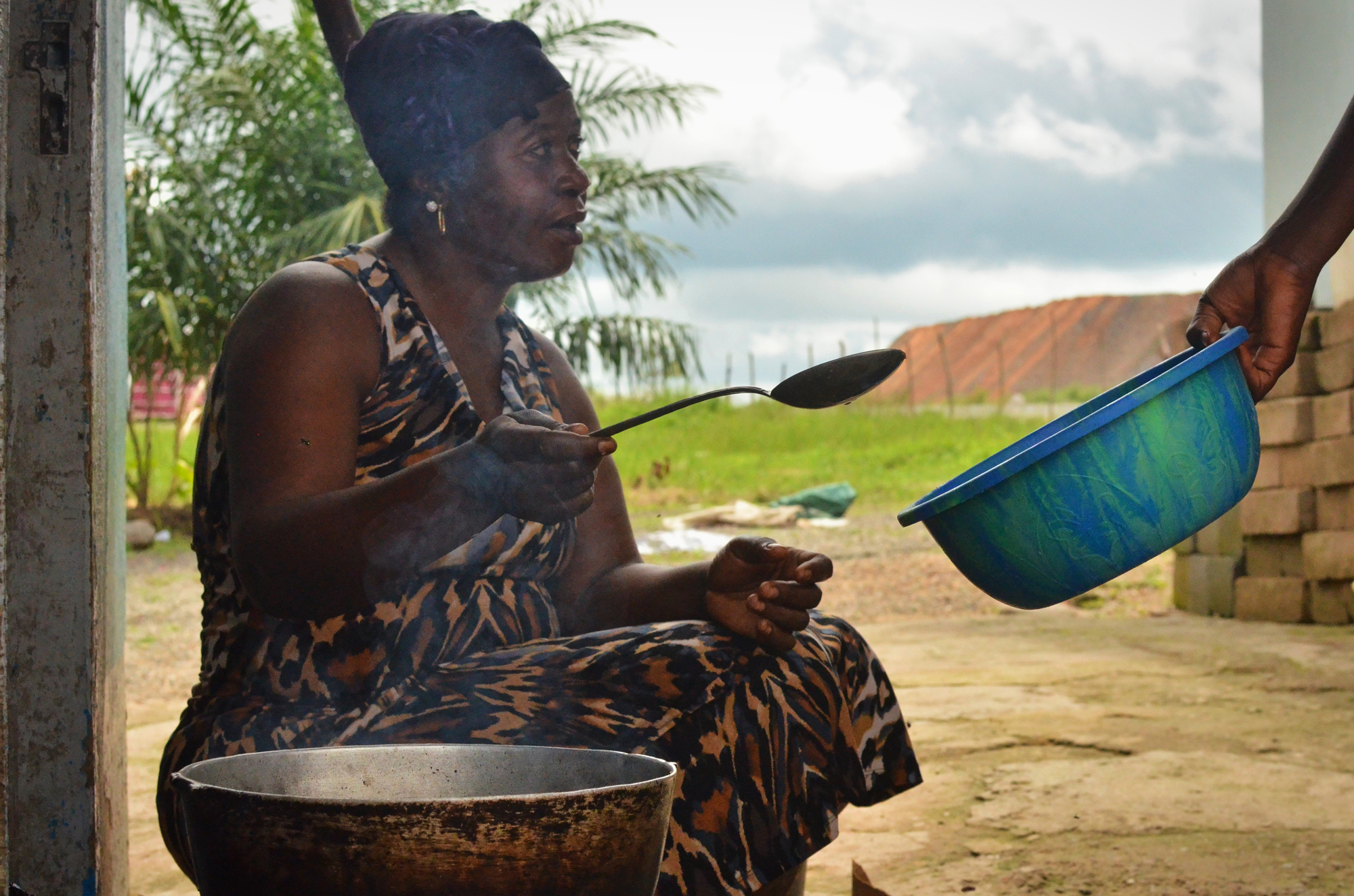 Jariatu Kamara, the wife of a local chief, was one of several people moved to the resettlement site in 2010 after the mine's safety zone was expanded to 500 meters. She says that the new house is a welcome improvement to their old property.