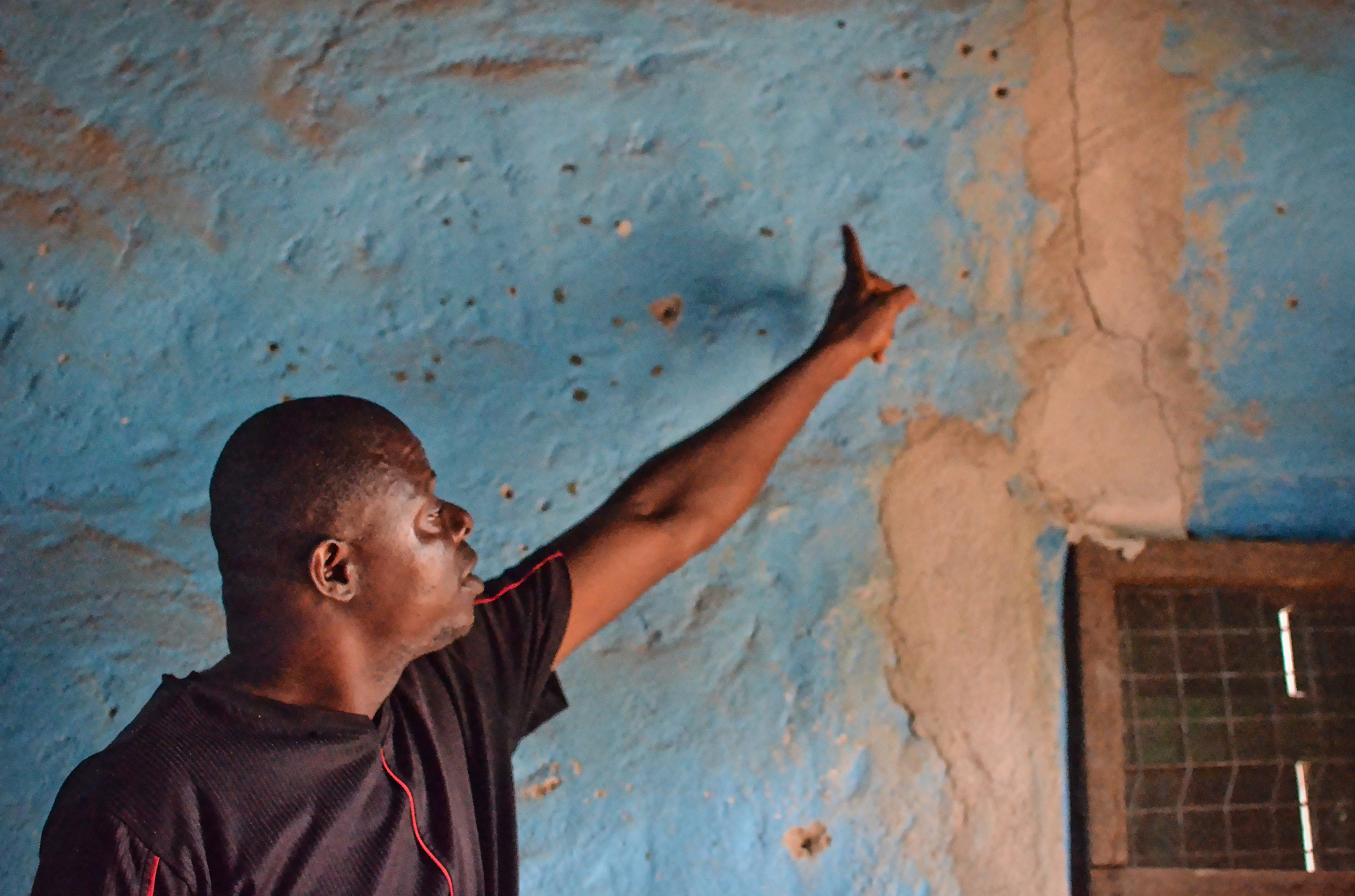 A Koidu resident points out one of the cracks in his house, which he says was caused by vibrations coming from by the mine's bi-weekly blasts. Many structures in Koidu suffer similar cracks.