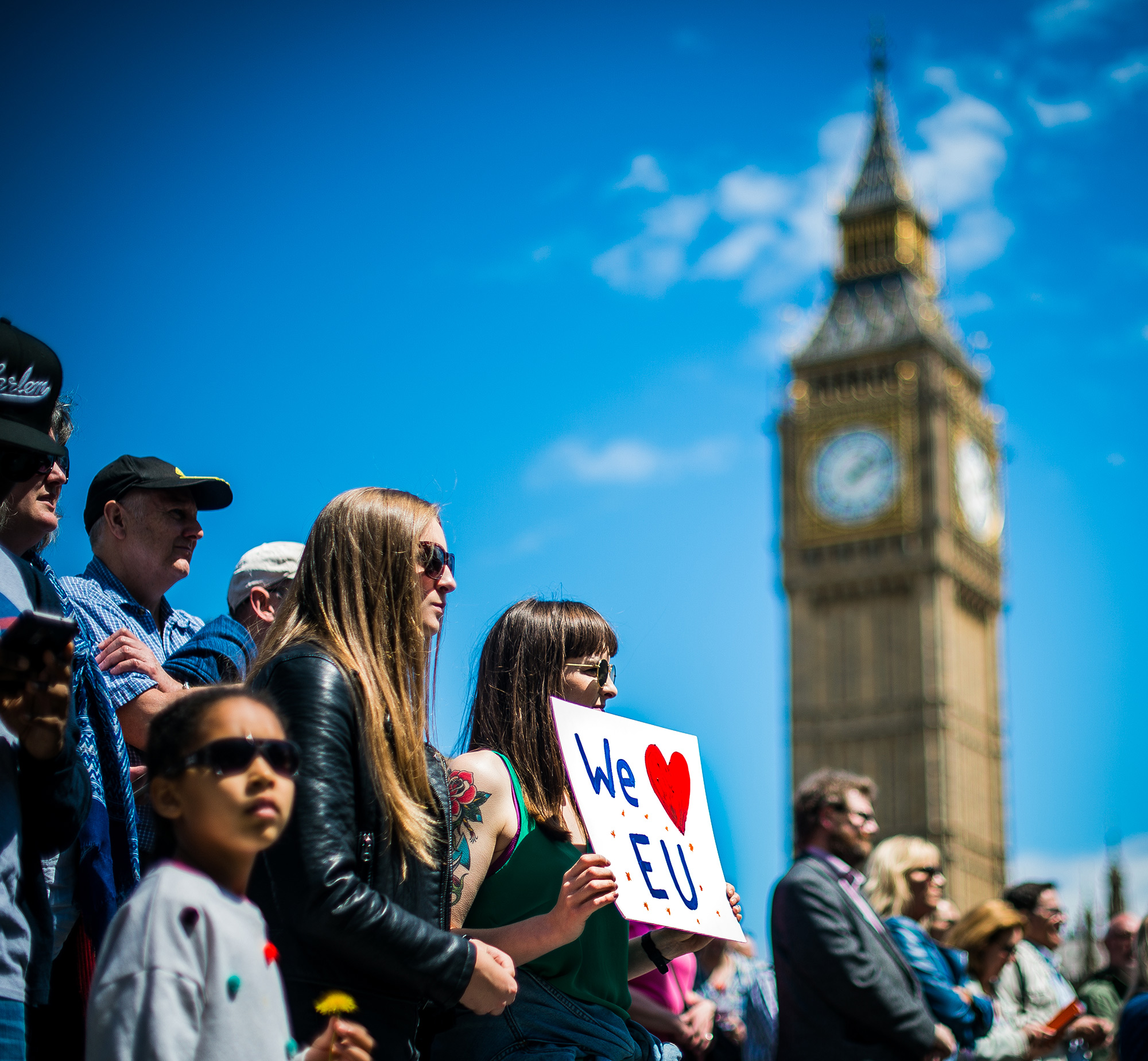 A young woman holds up a sign in favor of the European Union at the 'March for Europe' protest on July 2, London's Big Ben visible in the sky above. (Photo by Garon S/Flickr User)