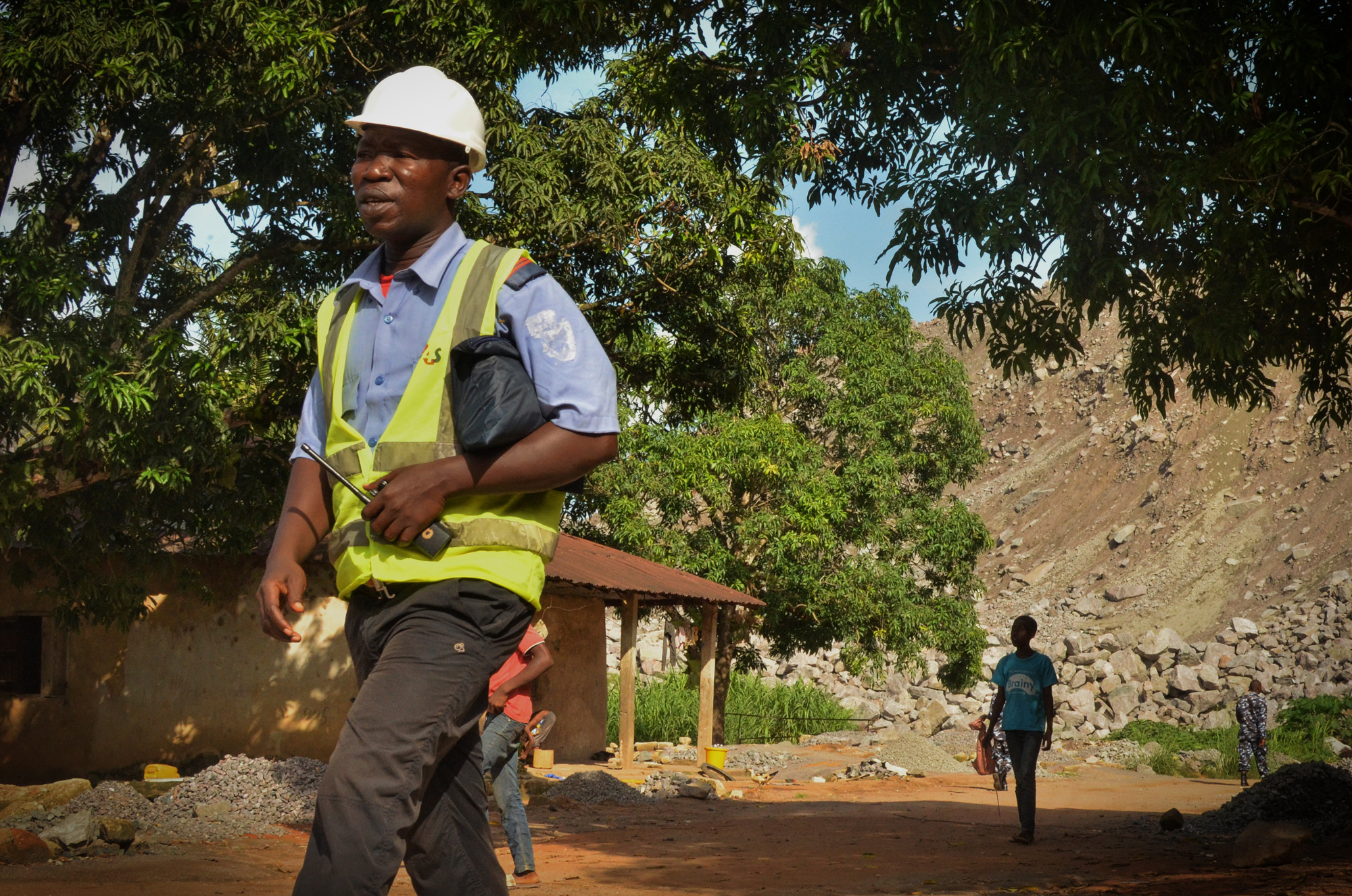 Koidu residents living within the mine's 500-meter safety zone are escorted by police and private security officers to safety checkpoints, where they wait for the mine's bi-weekly blasting to pass.