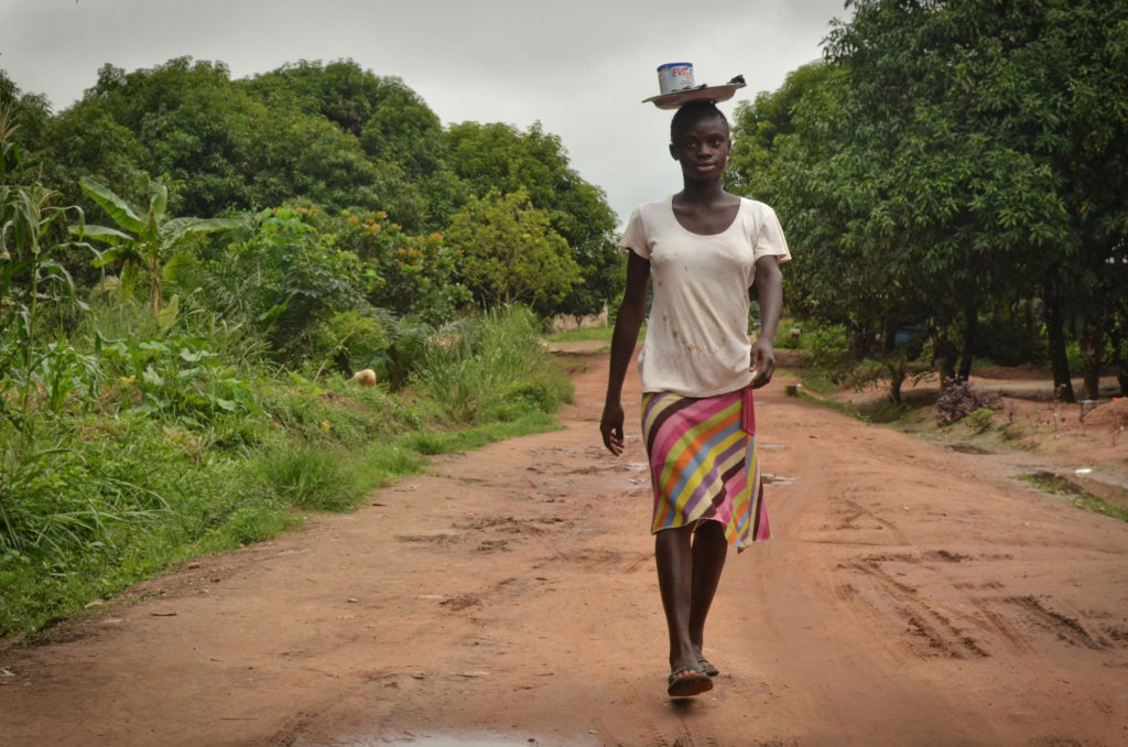 Sia Momoh's father, an artisanal miner named Aiah Momoh, was shot and killed by police in 2007 while protesting mining activity. Sia, now 15 years old, lives with her aunts and grandmother and spends her days selling produce and butterscotch around town.