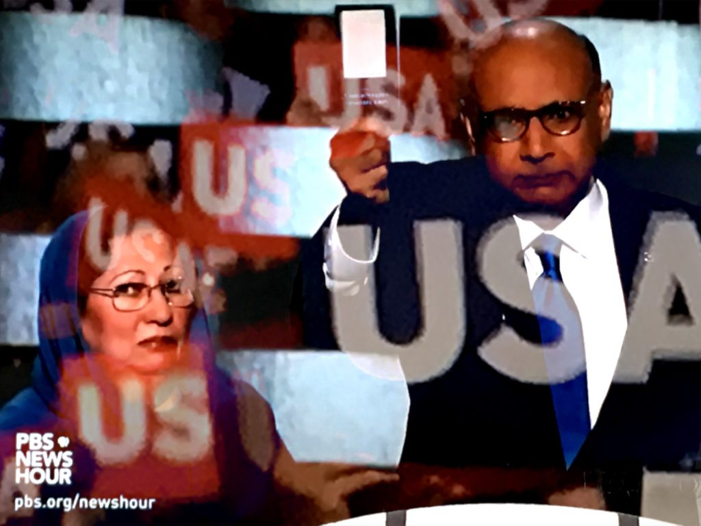 Parents of fallen U.S. Army Captain Humayun Khan, Ghazala and Khizr Khan, address the DNC, displaying a copy of his pocket U.S. Constitution. (Composite image by Biz Herman/GroundTruth)
