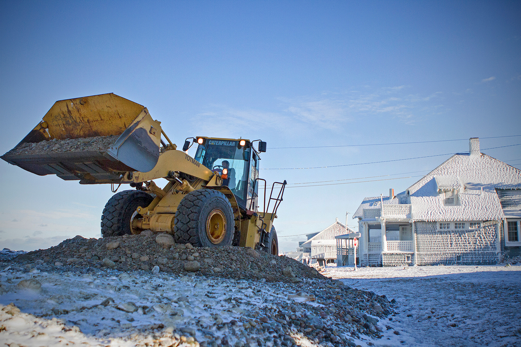 A wheel loader scoops up detritus from the ocean while rebuilding a road in Scituate following a 2015 winter storm that flooded dozens of homes, destroyed streets and power lines and even pulled buildings into the sea. Some homes in the town have been damaged and rebuilt more than 10 times with funding from the federal government and community tax money. (Photo by Lauren Owens Lambert/GroundTruth)