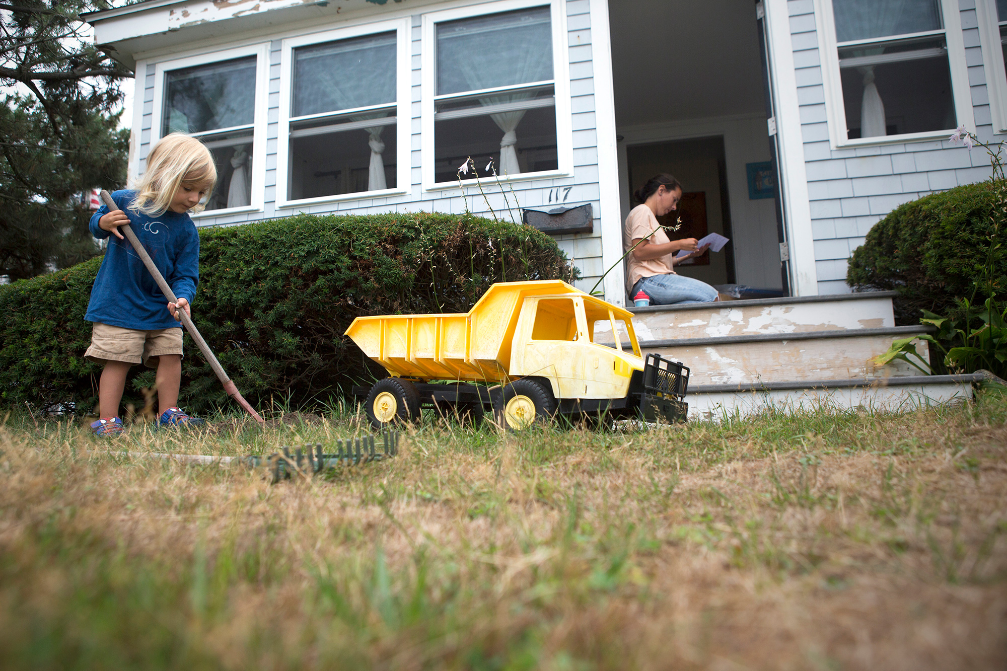 Scituate resident Devon Barrie and her son, Kailub Sullivan, live along the beach in Scituate near the new town seawall under construction. Sullivan likes to imitate the working crew with a toy dump truck, moving dirt from one side of the yard to the other. (Photo by Lauren Owens Lambert/GroundTruth)