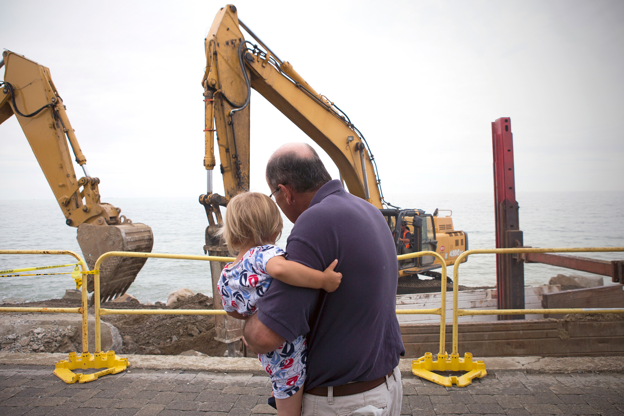 """Scituate resident Peter Caruso observes the construction of a new seawall in Scituate with his grandson, Santo Arias. The town hopes that bolstering the seawall will mitigate the severity of winter storms and the effects of sea level rise. """"It is a tough spot to try and live and the storms are more frequent than they use to be,"""" says Caruso. (Photo by Lauren Owens Lambert/GroundTruth)"""