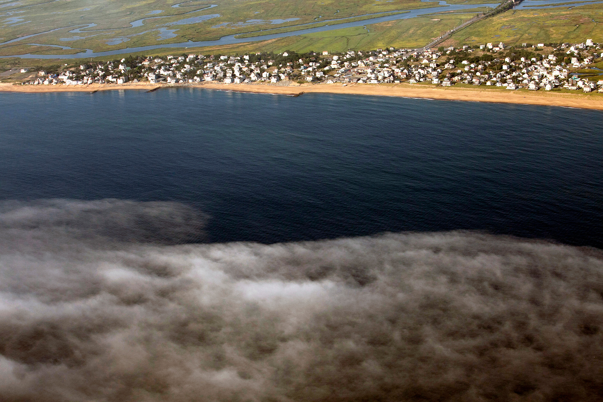 """Homes and businesses on Plum Island come face-to-face with the Atlantic Ocean. """"The big problem with climate change and sea level rise is that it's a slow motion disaster and people don't really perceive that it's happening,"""" says Mike Morris of Storm Surge, a nonprofit organization in nearby Newburyport that helps communities prepare for the effects of climate change. (Photo by Lauren Owens Lambert/GroundTruth)"""