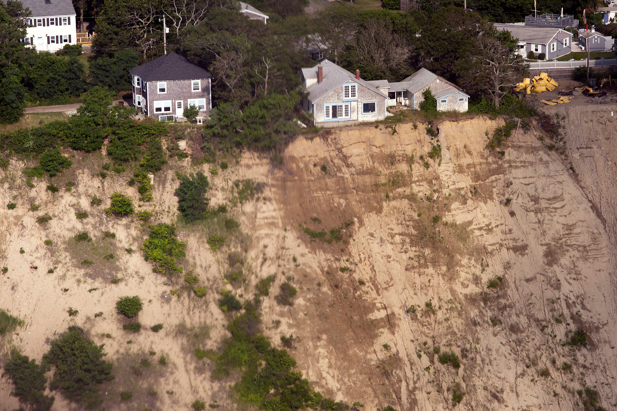 Homes hover dangerously close to the cliff's edge in Plymouth, on the South Shore of Massachusetts. With up to 68 percent of beaches on the East Coast eroding, some residents are moving out. But many are not budging, choosing instead to bolster their homes and adapt to climate change. (Photo by Lauren Owens Lambert/GroundTruth)