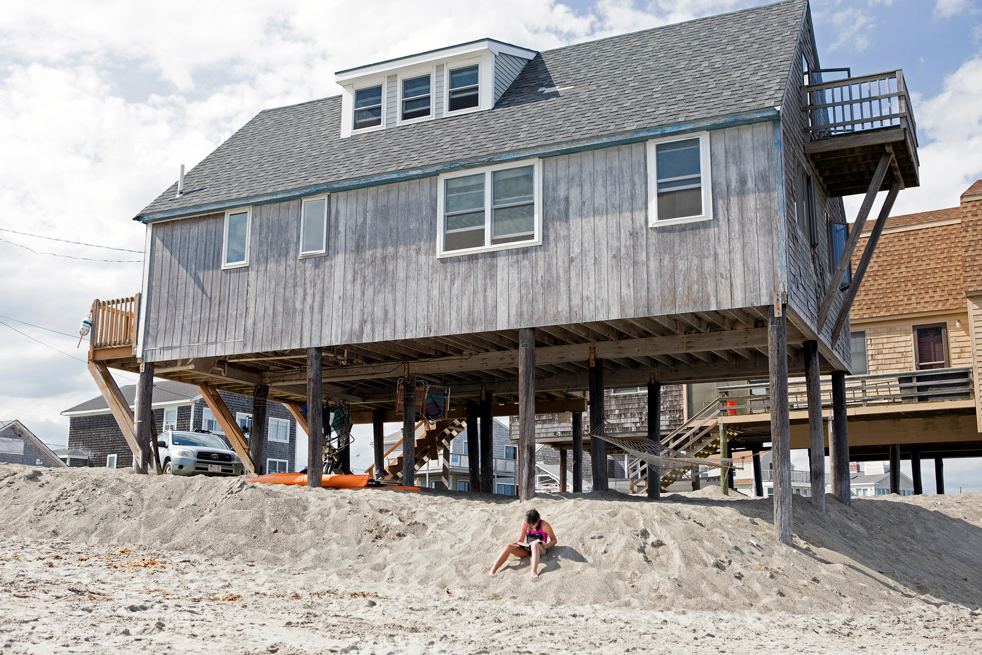 A girl reads her book by a raised cottage on Peggotty Beach in Scituate, on the South Shore of Massachusetts. Where there were once more than 50 cottages, the number has dwindled to a dozen as storms have eroded the beach and forced homeowners to vacate the area. Those houses that remain have been moved onto stilts. (Photo by Lauren Owens Lambert/GroundTruth)