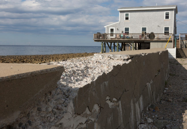 Next to a raised home in Scituate, a seawall crumbles—the result of years of ocean waves pummeling the shores. Most coastal towns along the Massachusetts South Shore have man-made sea walls in place to help protect the ocean front from storm surges. But recent storms have breached the seawalls and weakened them for future storms. (Lauren Owens Lambert/GroundTruth)