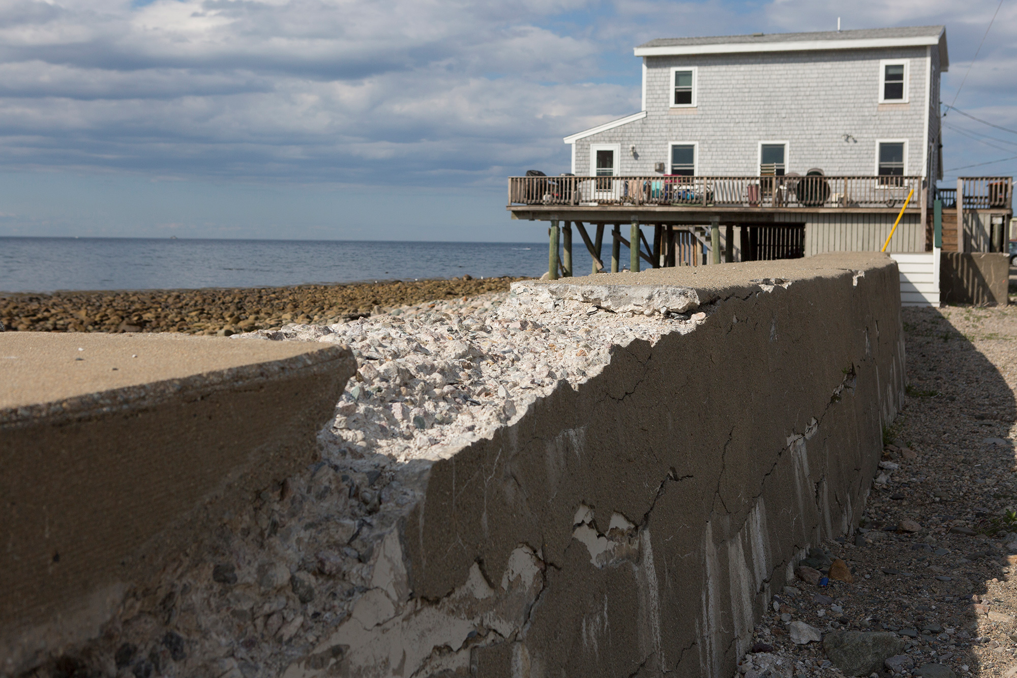 Next to a raised home in Scituate, a seawall crumbles—the result of years of ocean waves pummeling the shores. Most coastal towns along the Massachusetts South Shore have man-made sea walls in place to help protect the ocean front from storm surges. But recent storms have breached the seawalls and weakened them for future storms. (Photo by Lauren Owens Lambert/GroundTruth)