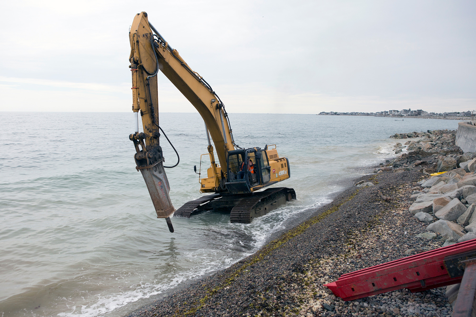 A wheel excavator travels up the rocky shore south of Egypt Beach in Scituate as construction workers rebuild a damaged seawall, originally built in the 1930s. The crew is increasing its height and strength with additional steel support and rocks. (Photo by Lauren Owens Lambert/GroundTruth)