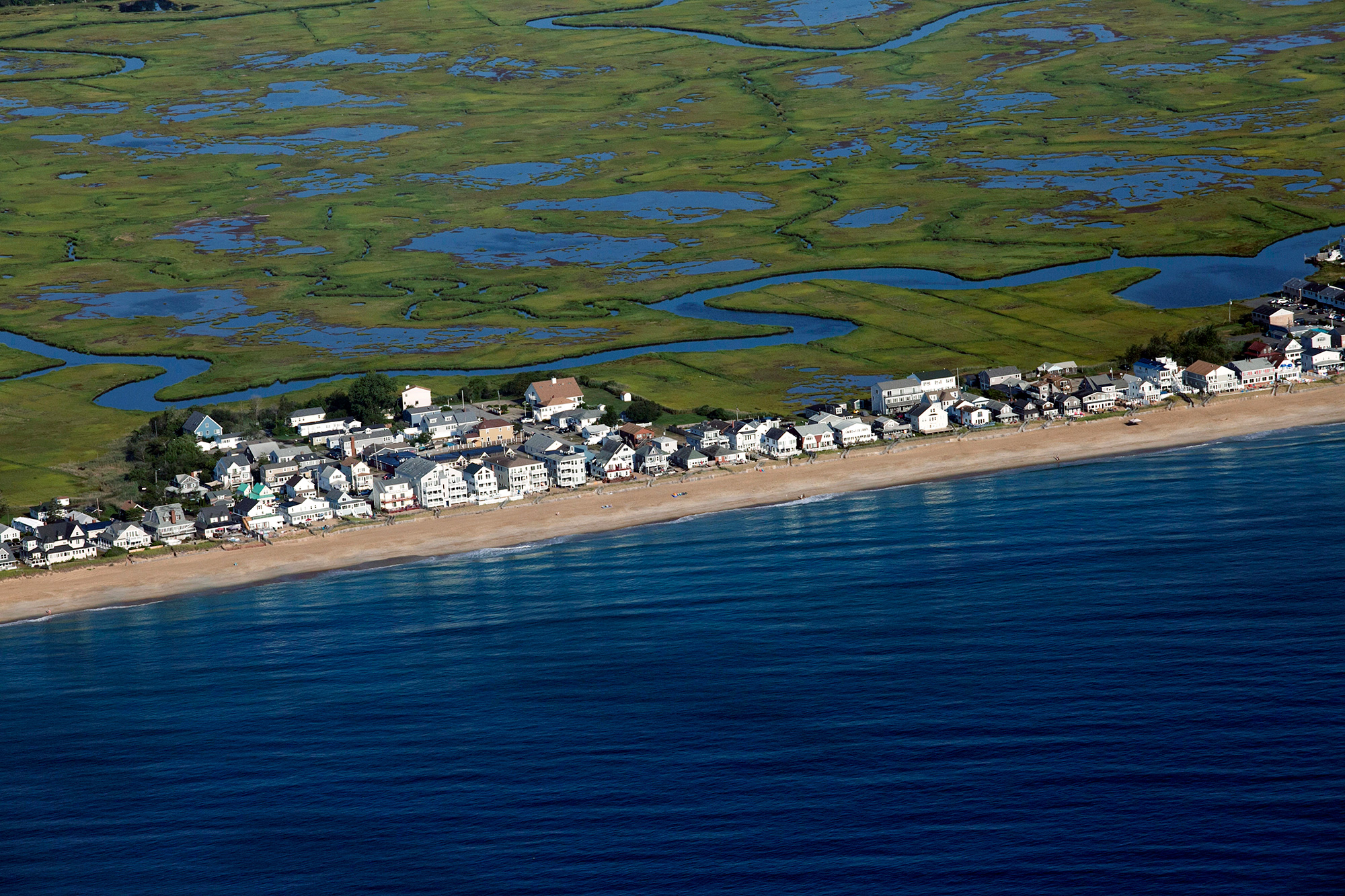 Homes along Salisbury Beach in Massachusetts and neighboring Hampton Beach in New Hampshire  face the Atlantic Ocean and are backed by miles of marsh. As sea level rise elevates the water table, flooding can come from the marsh instead of the ocean. (Photo by Lauren Owens Lambert/GroundTruth)