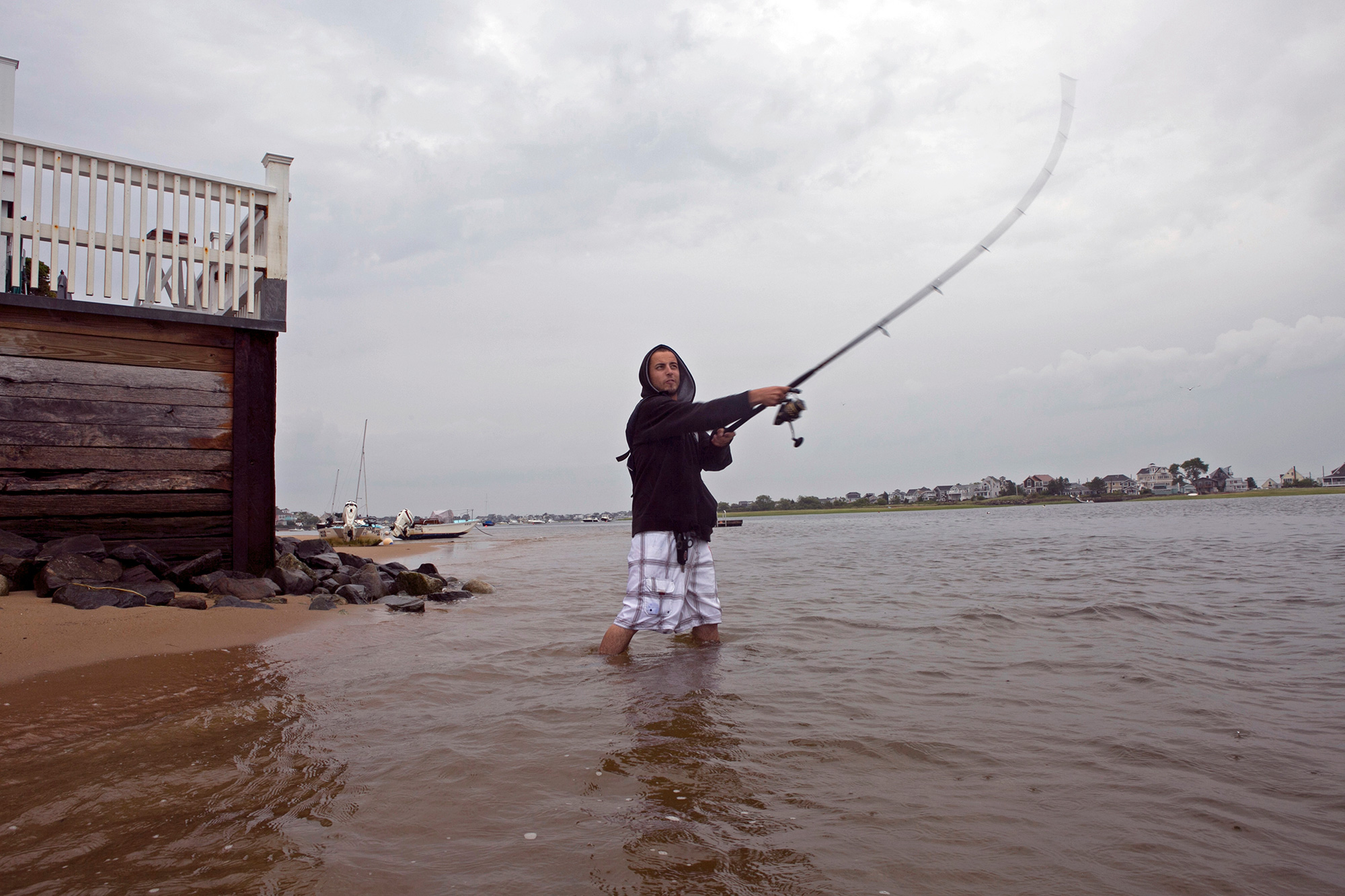 Marcos Rego fishes for striped bass on Plum Island early in the morning. During high tide, the water slaps against the building behind him. (Photo by Lauren Owens Lambert/GroundTruth)