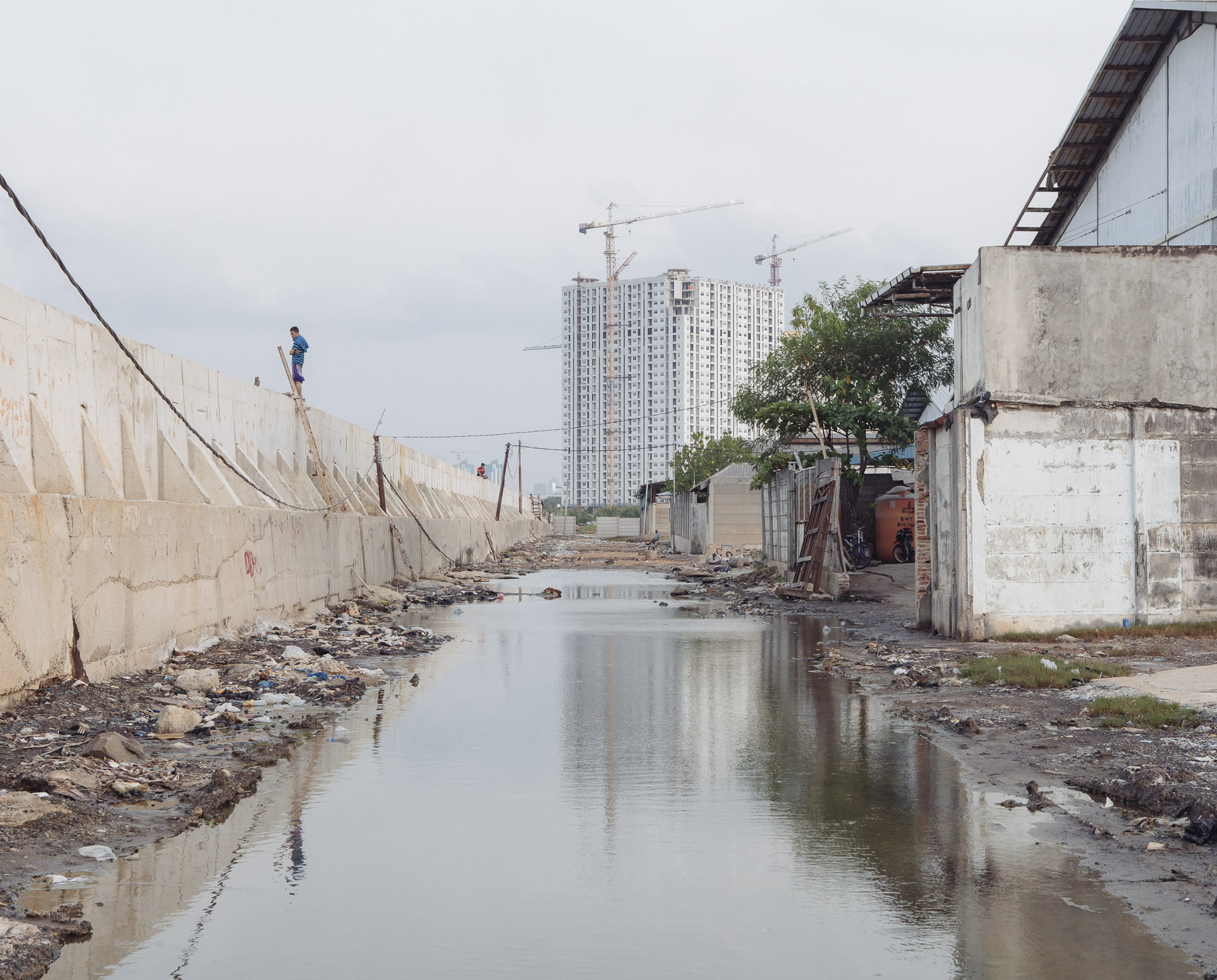 This recently-reinforced section of seawall in Muara Baru, North Jakarta, fails to prevent flooding since seawater still creeps through the soil. This area, once booming with various businesses, is currently abandoned. (Photo by Muhammad Fadli/GroundTruth)