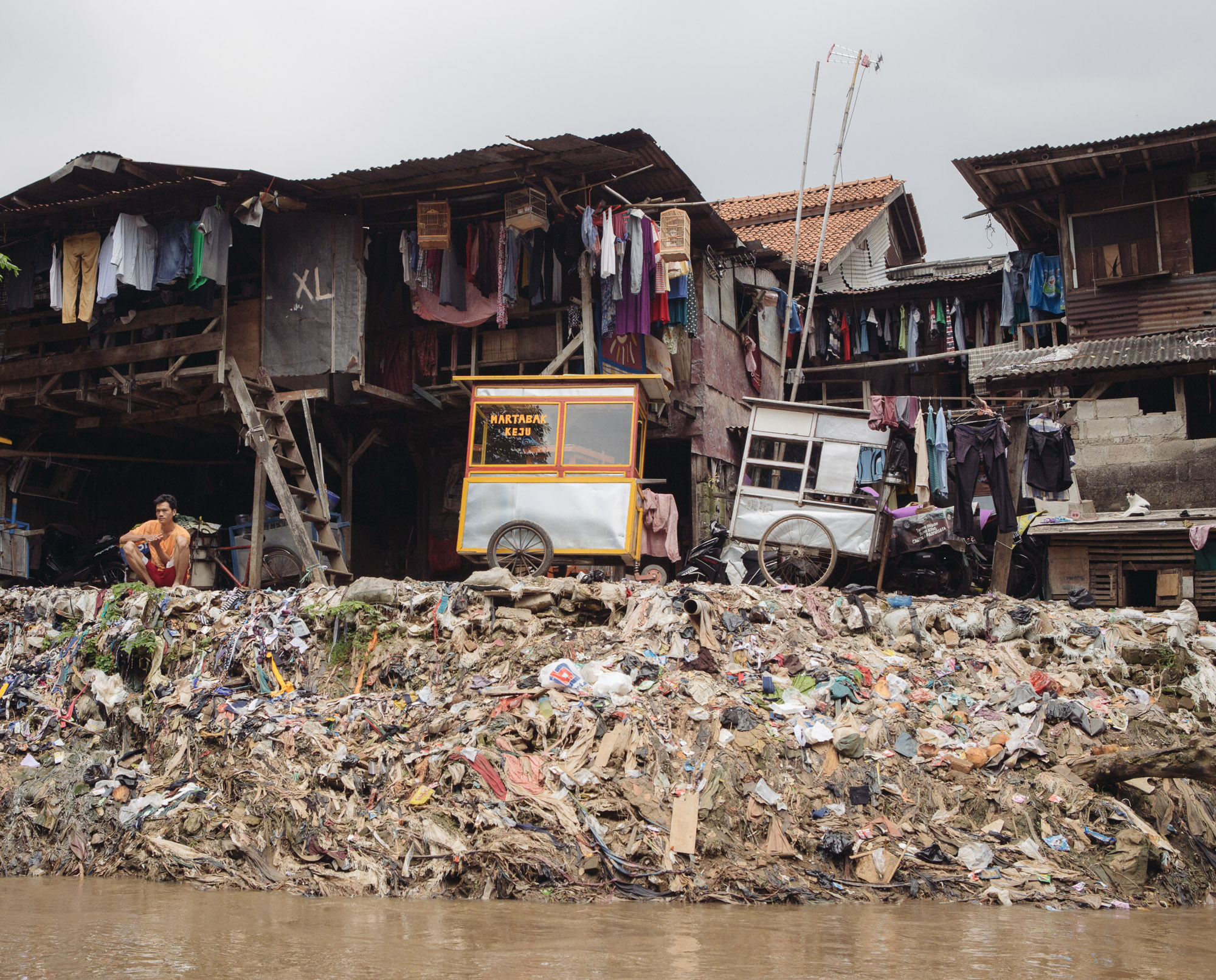 Slums line the Ciliwung river. As Jakarta's government seeks to revitalize the rivers to prevent flooding, hundred of thousands of people living on the banks are preparing for their eviction. (Photo by Muhammad Fadli/GroundTruth)