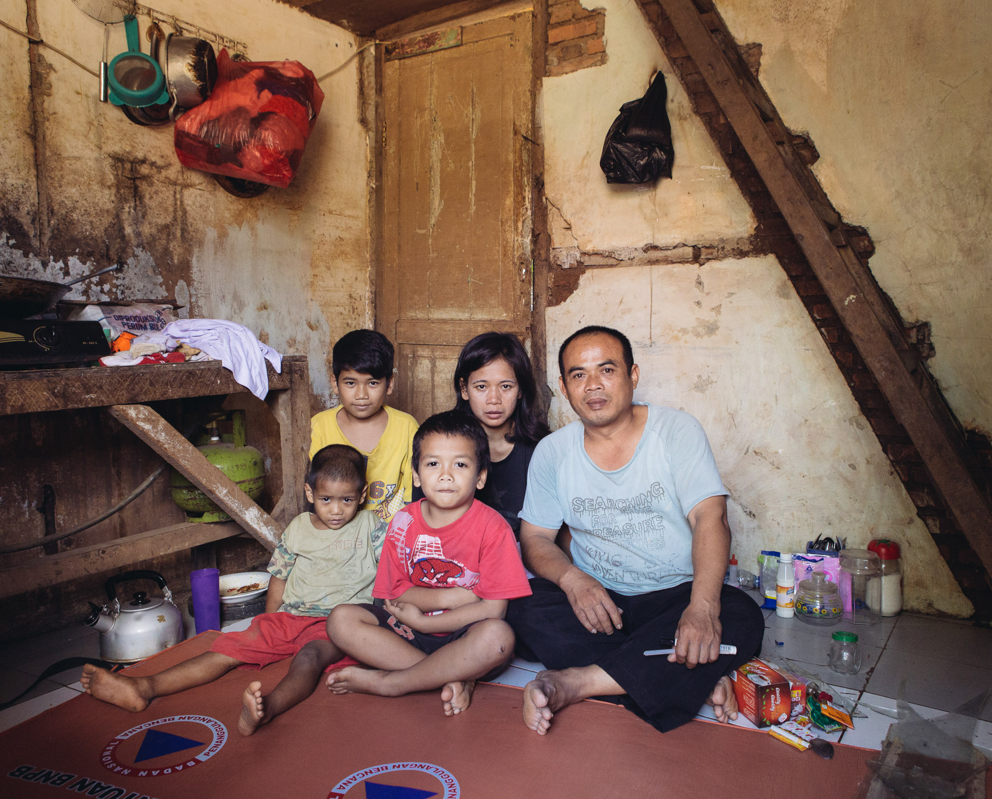 Residents living on the bank of the Ciliwung River pose for a photo in Kampung Melayu. Muhammad Syarifudin and Emi Wijayanti sit along with their three children. (Photo by Muhammad Fadli/GroundTruth)