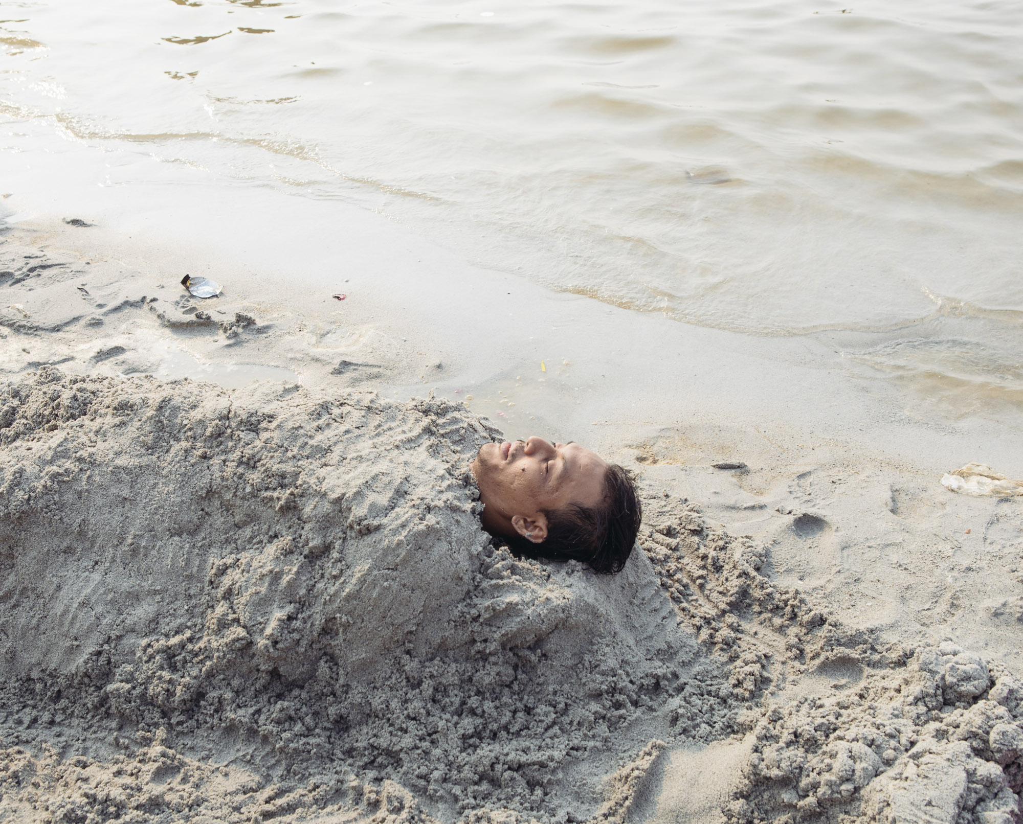 A man buries himself in the sand at Ancol Beach in North Jakarta. Ancol is popular among Jakarta's middle class on weekends, as it offers amusement parks, resorts and the only remaining accessible beach in the city. (Photo by Muhammad Fadli/GroundTruth)