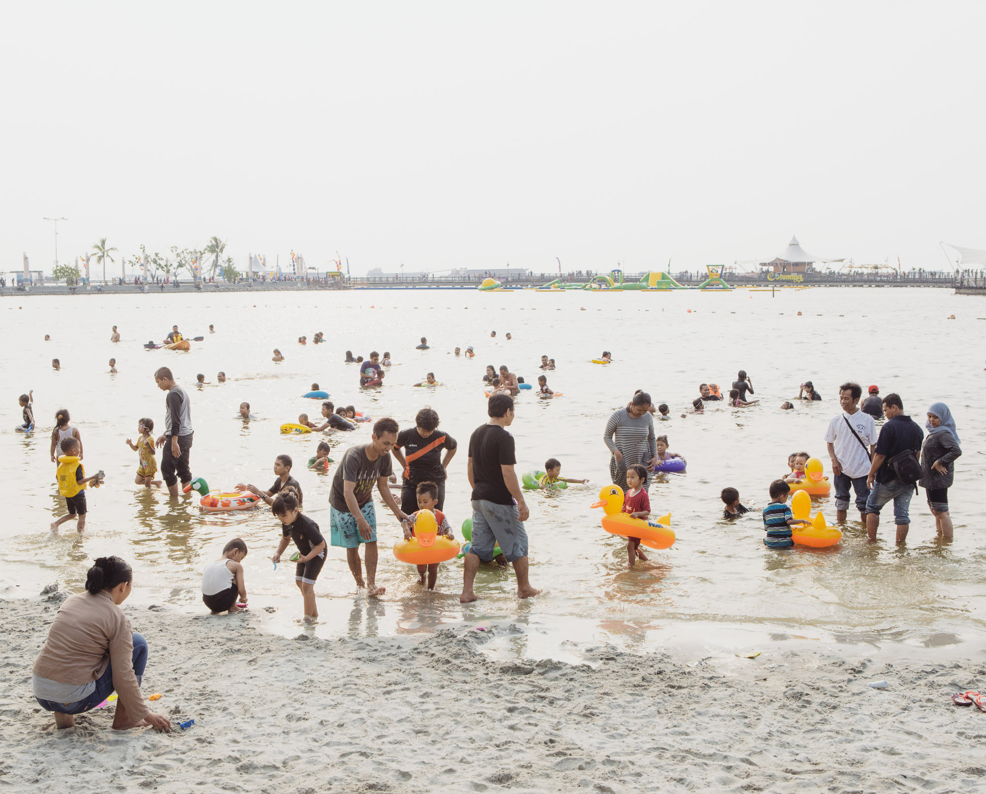 People spend their weekend at Ancol Beach in North Jakarta. Ancol is popular among Jakarta's middle class, as it offers amusement parks, resorts and the only remaining accessible beach in the city. However, the beach is very much artificial. (Photo by Muhammad Fadli/GroundTruth)