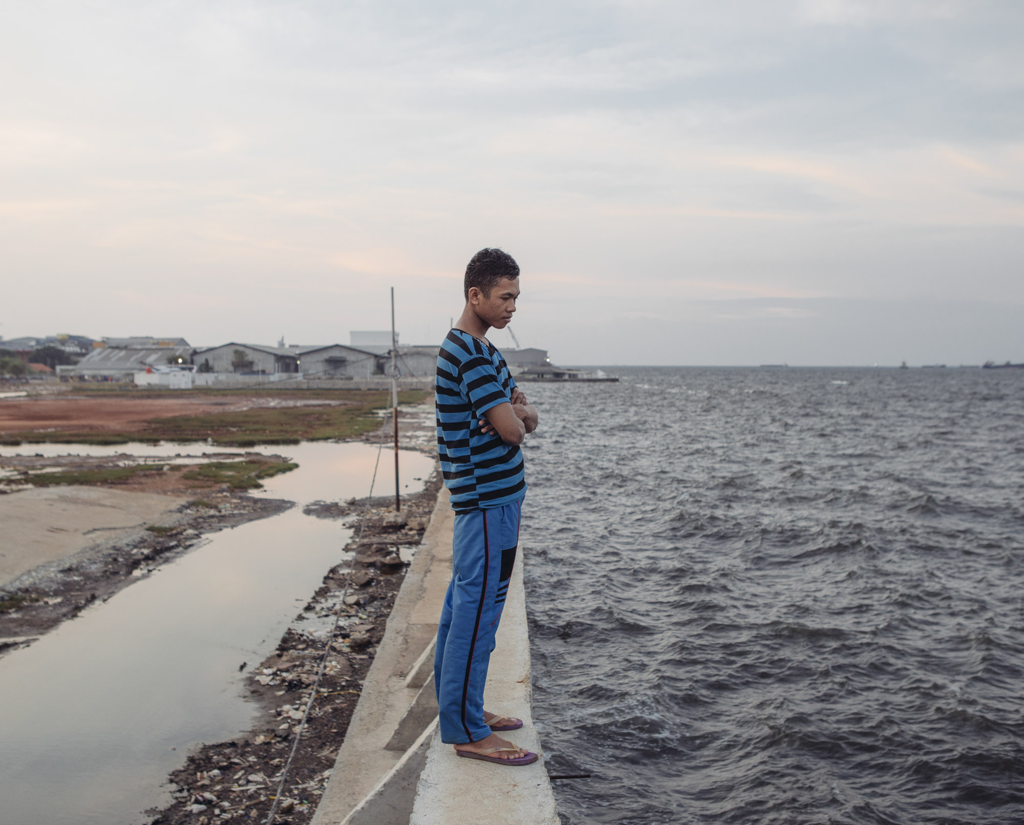 "Feri Yadi, a resident of Muara Baru in North Jakarta, stands atop the recently-built seawall that protects the district where he lives. He has little confidence that the seawall will work as expected. ""Like in the past, this will be broken somehow,"" he said. (Photo by Muhammad Fadli/GroundTruth)"