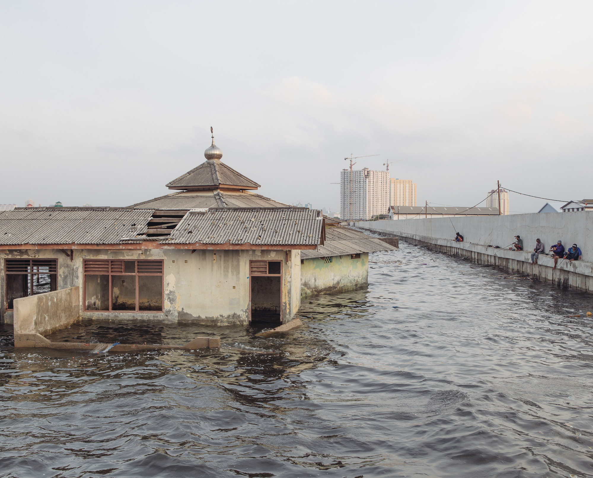 An abandoned mosque outside the sea wall in Muara Baru, North Jakarta, drowns in high water levels. Jakarta is sinking as a result of massive groundwater extraction. – and Muara Baru, one of the worst-sinking parts of the city, is already located below the sea level. (Photo by Muhammad Fadli/GroundTruth)