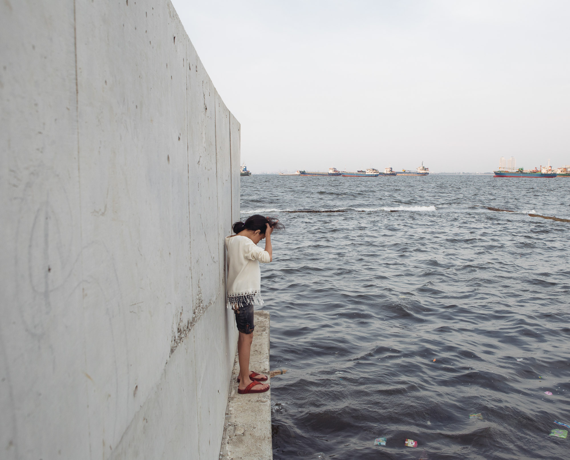 A girl stands at the outer side of the recently-reinforced seawall in Muara Baru, Penjaringan, North Jakarta. The city is sinking as a result of massive groundwater extraction, and Muara Baru, one of the worst sinking part of Jakarta, is already located below the sea level. (Photo by Muhammad Fadli/GroundTruth)