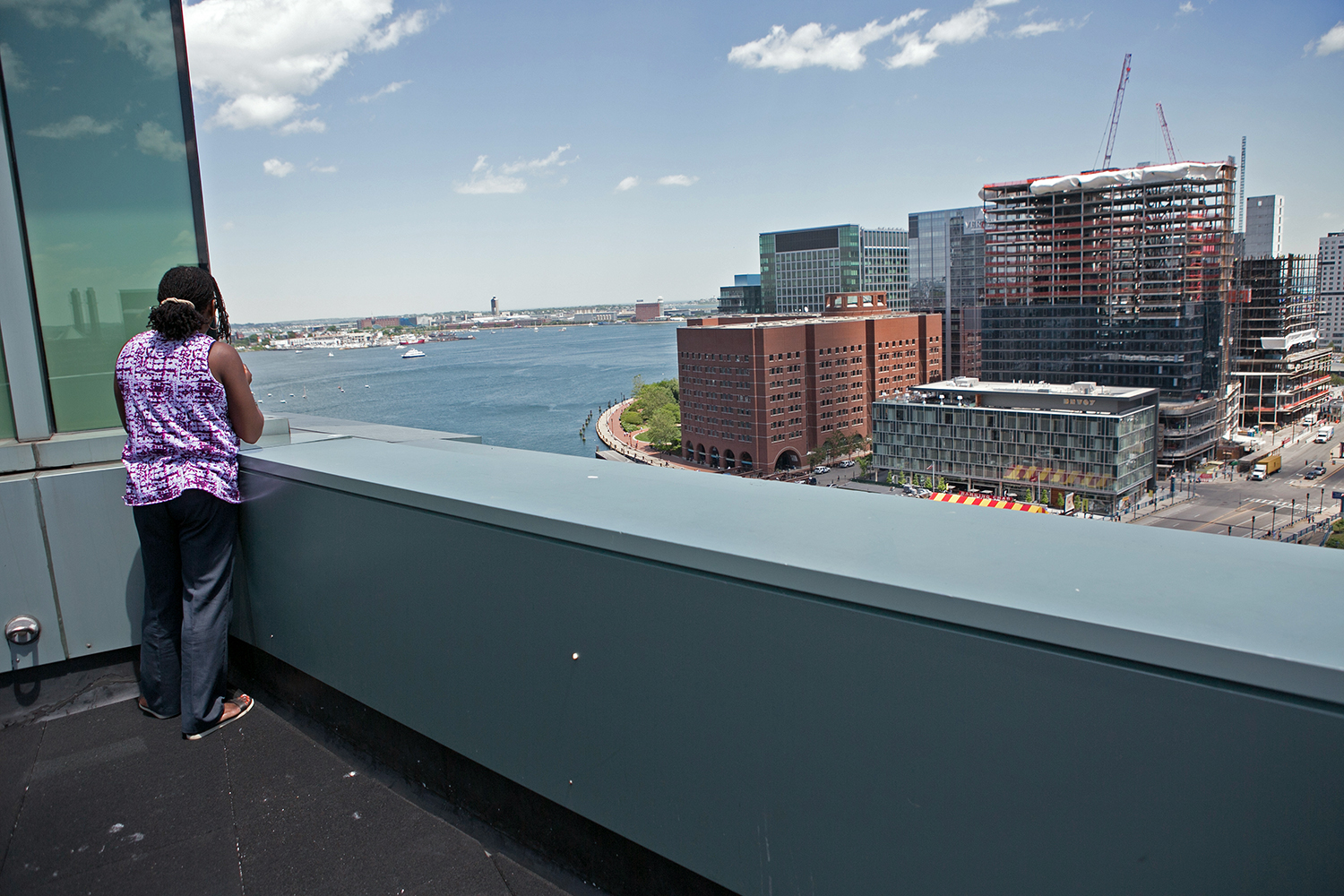 Movita Harrigan looks out on a new development in South Boston, June 6, 2016. (Photo by Lauren Owens Lambert/GroundTruth)