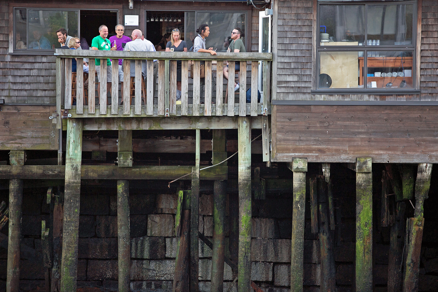 People eat and drink on top of old pilings at Boston Sail Loft restaurant in the North End on June 6, 2016. (Photo by Lauren Owens Lambert/GroundTruth)