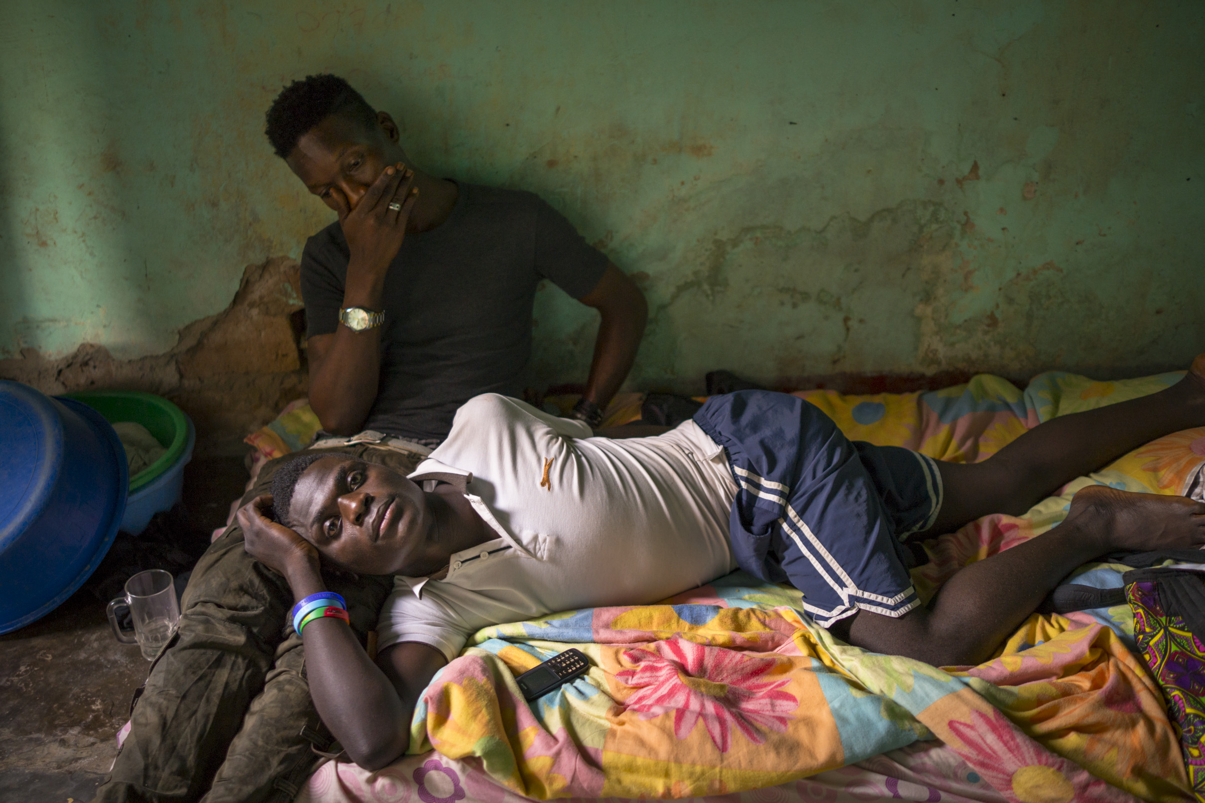 Jackson Mukasa lies on his bed, resting his head on the lap of his friend, Kim Mukisa, who has dropped by for a visit. The two were beaten and arrested in January 2014, accused of homosexuality. After 5 months in jail, their case was dismissed for lack of prosecution. After their release , they began life anew, having been robbed of their posessions. Mukisa, a clothing designer, also lost his atelier and shop in downtown Kampala. (Photo by Diana Zeyneb Alhindawi/GroundTruth)
