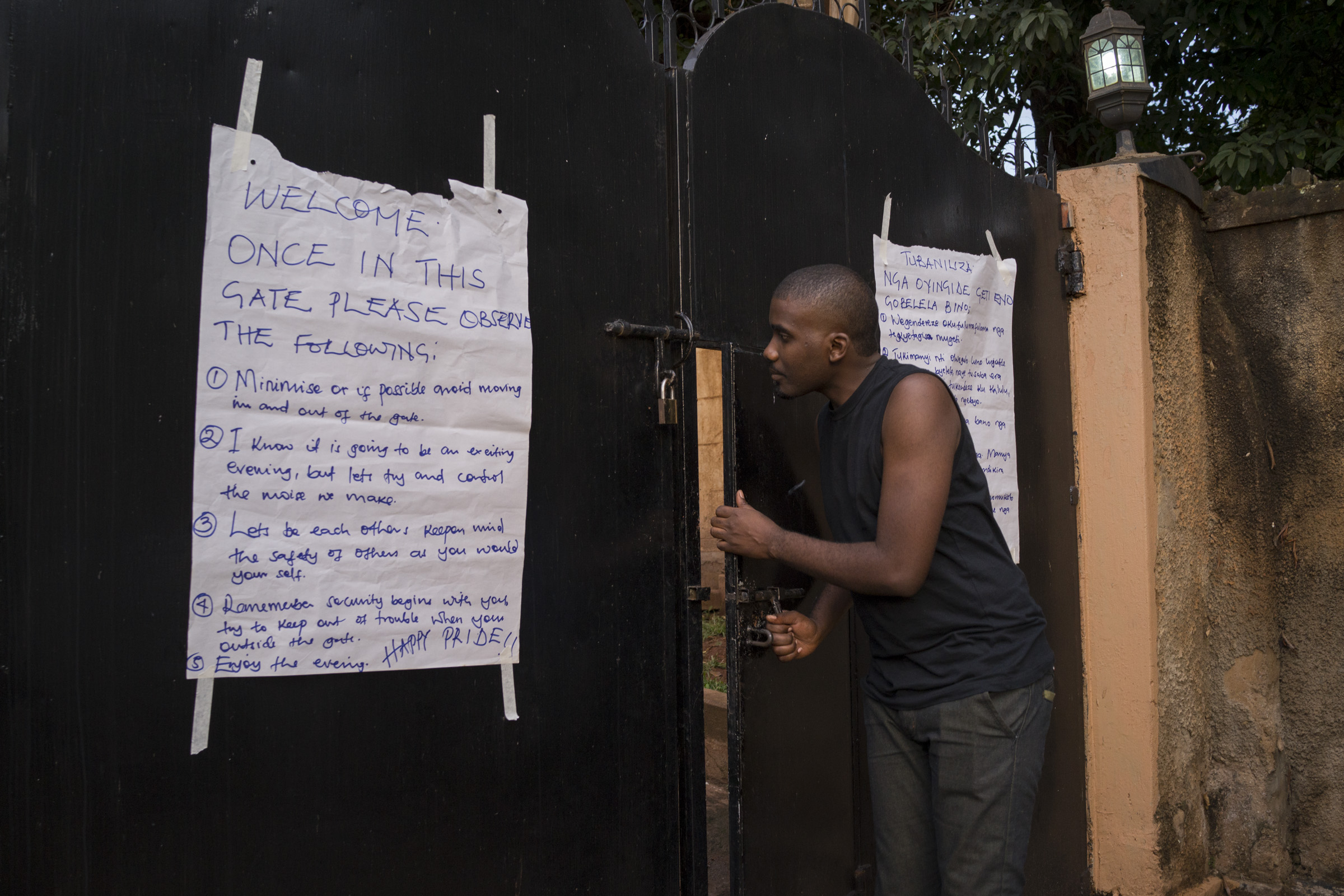 """The appointed gatekeeper opens the door to let in a member of the LGBT community. To ensure the security of particiants, events were held in """"secret,"""" at private locations that were disclosed to members of the LGBT community and their supporters just one or two days before an event. (Photo by Diana Zeyneb Alhindawi/GroundTruth)"""