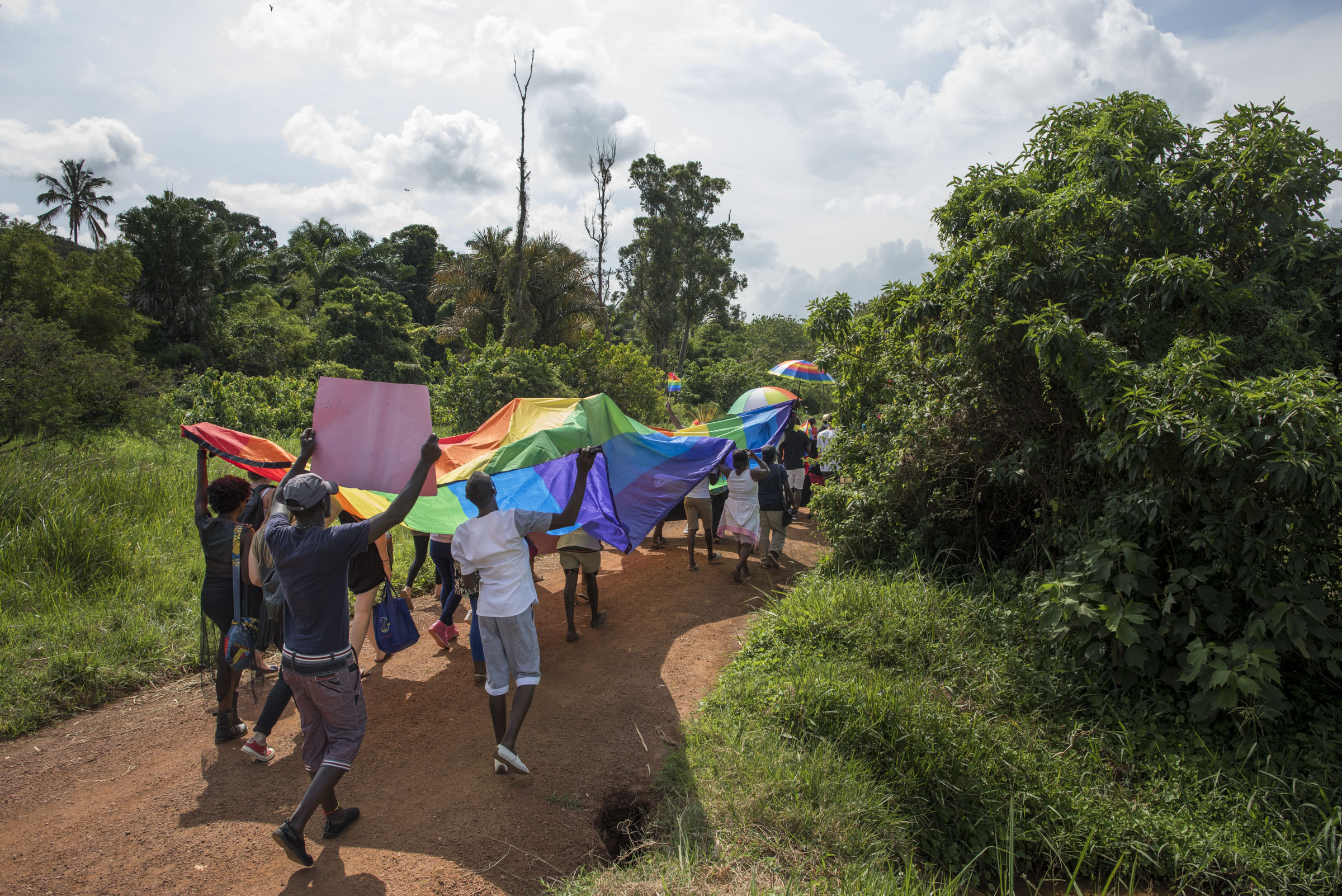 Members of the LGBT community and their supporters participate in a Pride march in a park on the banks of Lake Victoria in Entebbe, 40 km from Kampala. Safety concerns made it impossible to hold the march in a public location like downtown Kampala. (Photo by Diana Zeyneb Alhindawi/GroundTruth)