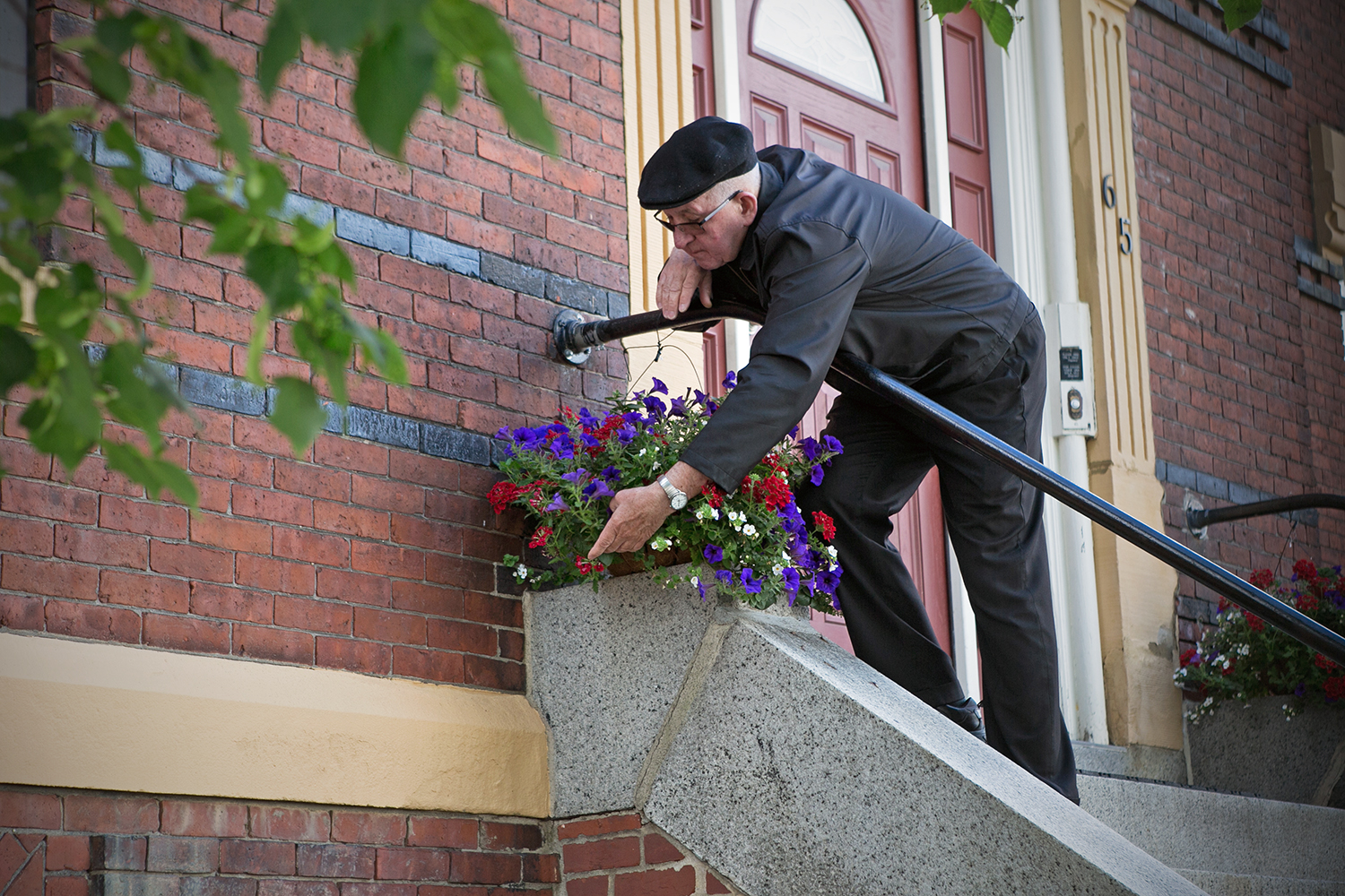 "Thomas Domurat, pastor at Most Holy Redeemer parish in East Boston tends to his flowers outside the church. ""We are located so low on the water table here, and the water table is rising. We might have to turn our basement into a swimming pool,"" says Domurat. (Photo by Lauren Owens Lambert/GroundTruth)"