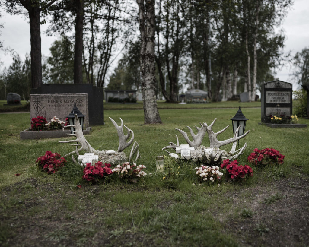 "The graves of Gustu and Heaika Marainen are decorated with flowers and antlers. On the grave, there are words in Swedish: ""It's hard to see in young days fresh flowers fall - it's hard to lose you, you were the joy for us all."" (Photo by Camilla Andersen/GroundTruth)"