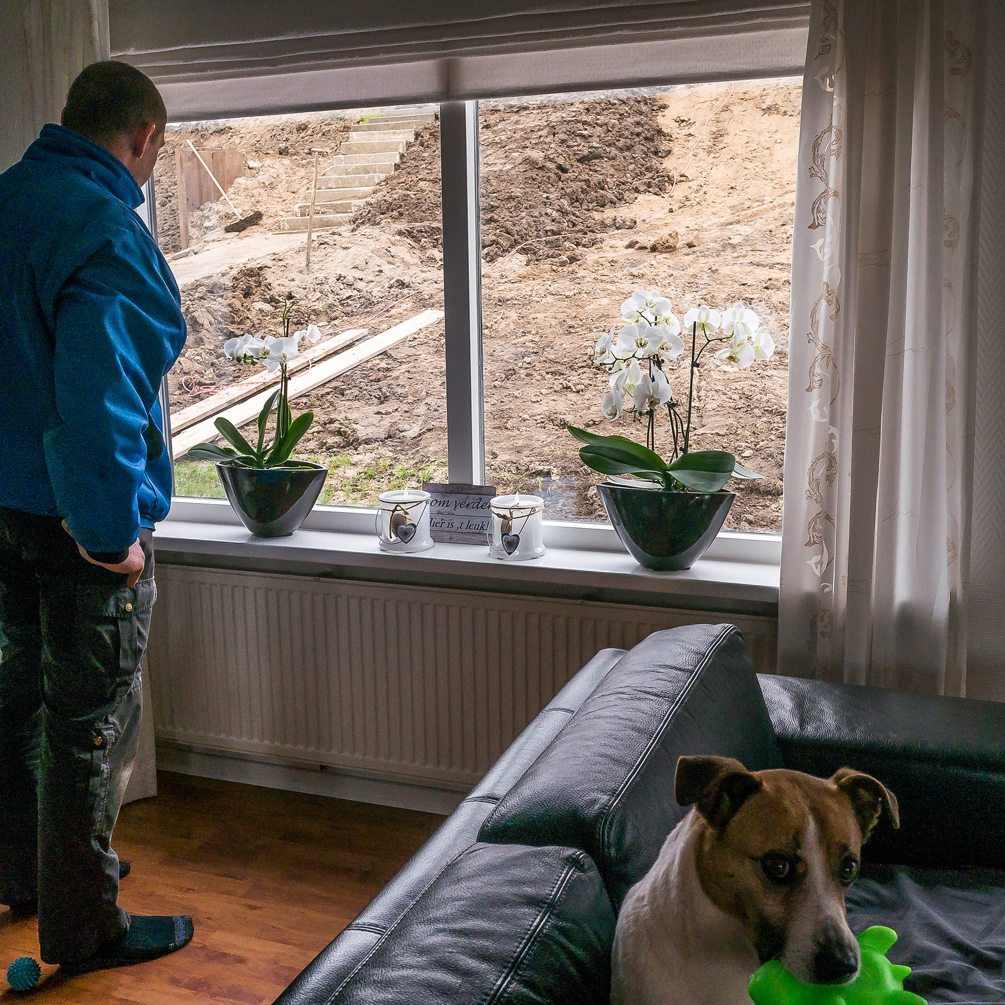 Police officer Ronald Hendriksa looks out at his front yard in Molenwaard, now a construction site for a national dike reinforcement project. The federal water authority first told him his house would be demolished, but negotiated to keep it. (Photo by Joris van Gennip/GroundTruth)
