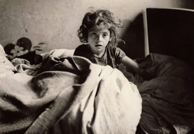 A young female refugee sits up in bed in France, 1940. (Photo by Martha Sharp/Sharp Family Archives)