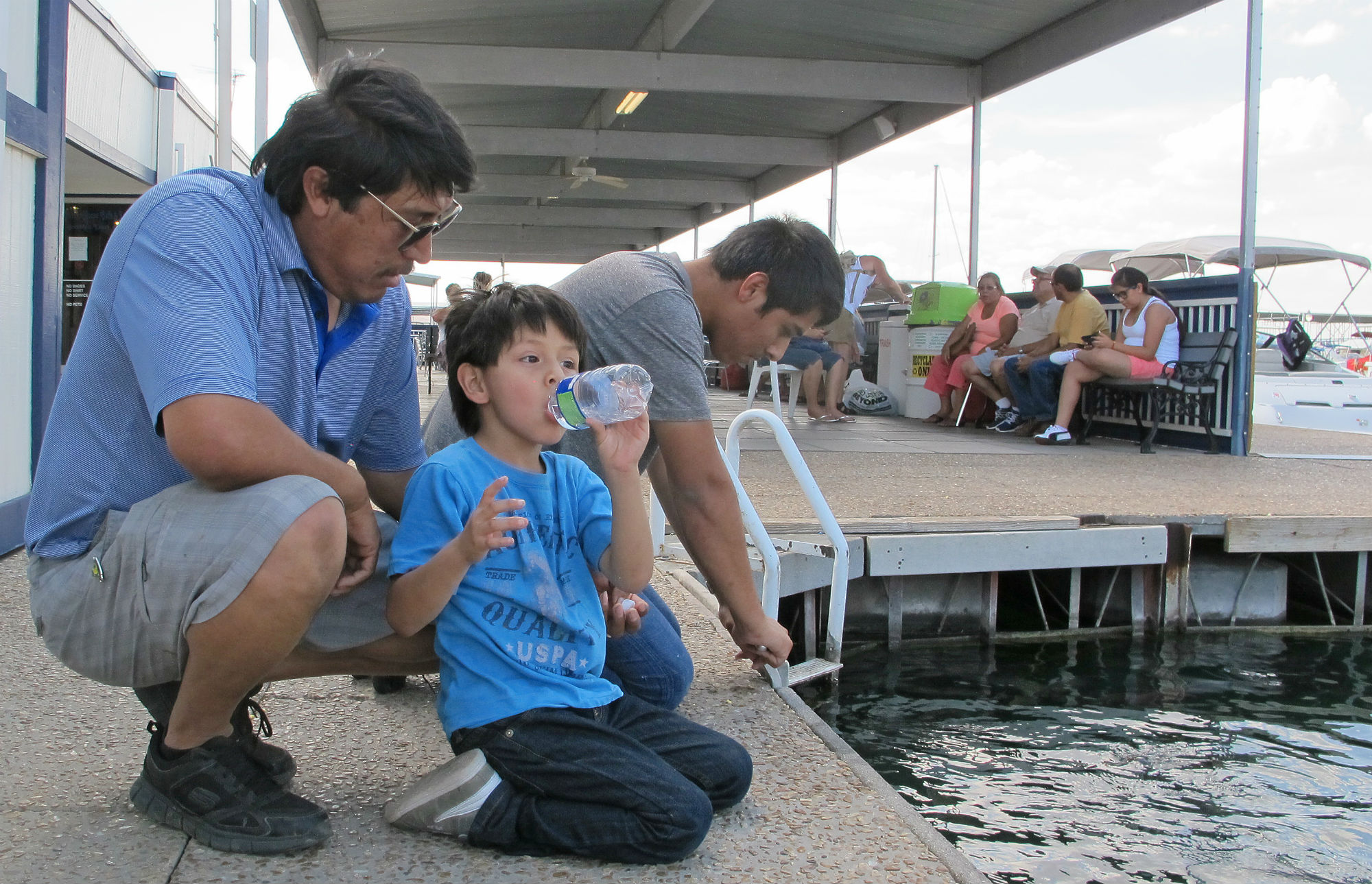 At the dock on one of the Grippentogs' marias, Raul Castro of Palm Springs, California, crouches by his two sons. Castro says that he brought them to Mead to teach them about the importance of water.
