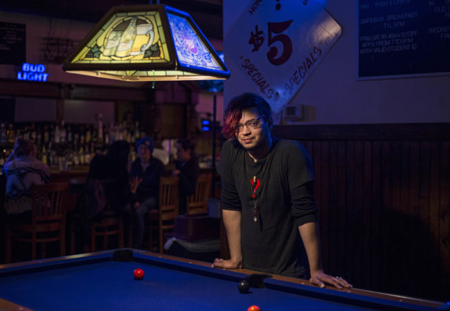 """Jody Ebejer, 22, a native of Detroit, poses at his workplace Honest John's in Midtown, on October, 24, 2016. Ebejer is now voting for independent candidate Jill Stein. """"People tell me that its really unrealistic, like don't throw your vote away, but I'm like, it's only throwing my vote away if I'm vote for someone who I don't agree with, who I don't feel represents me and my interest,"""" Ebejer said. (Photo by Brittany Greeson/GroundTruth)"""