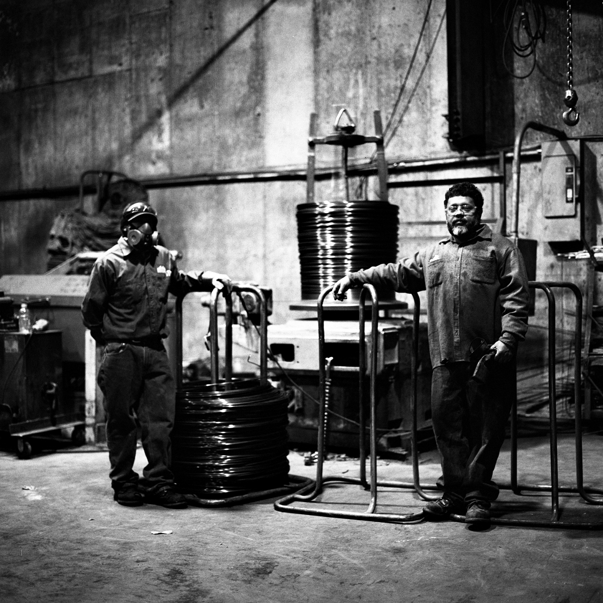 "Angel (left) and Wilfredo (right) –affectionally known as Mango – stand by their post at the wire straightener machine at Reinforcing Supply. The machine also acts as a stripper of any impurities which maybe stuck on the surface. This is the first step for the ""chair"" construction aspect of their business. ""Chairs"" are intricate bent and welded pieces of wire used as filler to help hold in place concrete when being poured for purposes such as sidewalks or the floor the workers themselves are standing on. A makeshift memorial for Thomas R. Dolphin was put up near the intersection of Meeker Avenue and Gardner Avenue in Greenpoint, Brooklyn, N.Y. (Photo by Dakota Santiago/GroundTruth)"