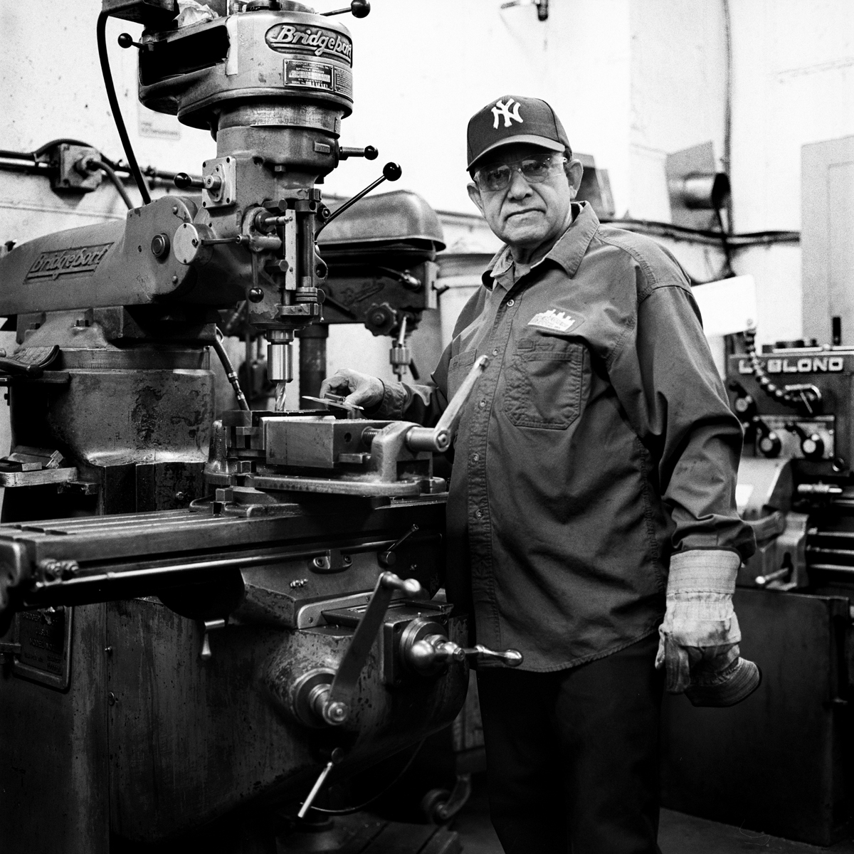 Mario, Reinforcing Supply shop machinist, stands by his driller. The machines used at Reinforcing Supply are all made and maintained in house. Williamsburg, Brooklyn, New York. A makeshift memorial for Thomas R. Dolphin was put up near the intersection of Meeker Avenue and Gardner Avenue in Greenpoint, Brooklyn, N.Y. (Photo by Dakota Santiago/GroundTruth)