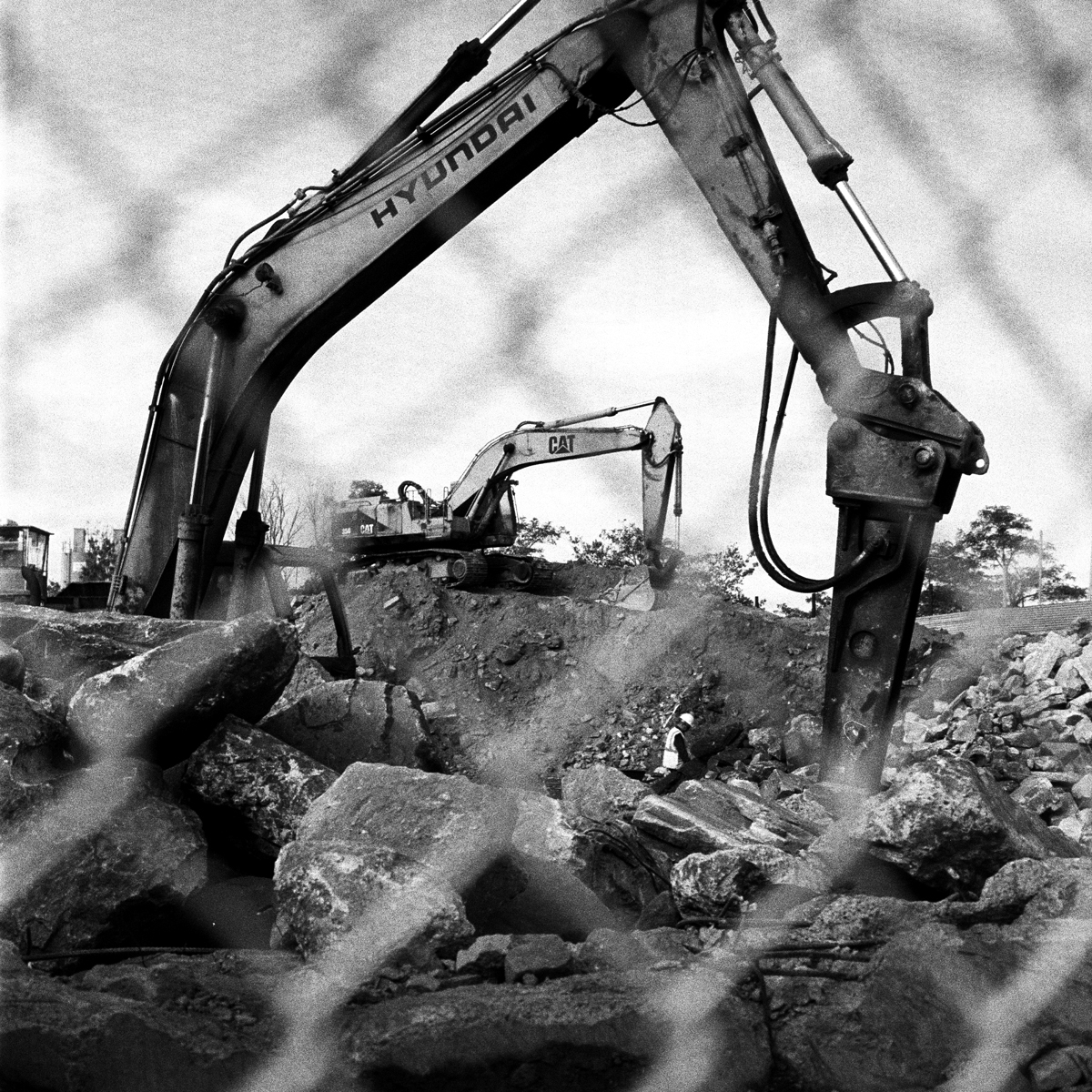 Workers between backhoe loaders break up old chunks of concrete and mince them into fine pebbles for reuse as filler on new concrete projects in Maspeth, Queens, New York. A makeshift memorial for Thomas R. Dolphin was put up near the intersection of Meeker Avenue and Gardner Avenue in Greenpoint, Brooklyn, N.Y. (Photo by Dakota Santiago/GroundTruth)