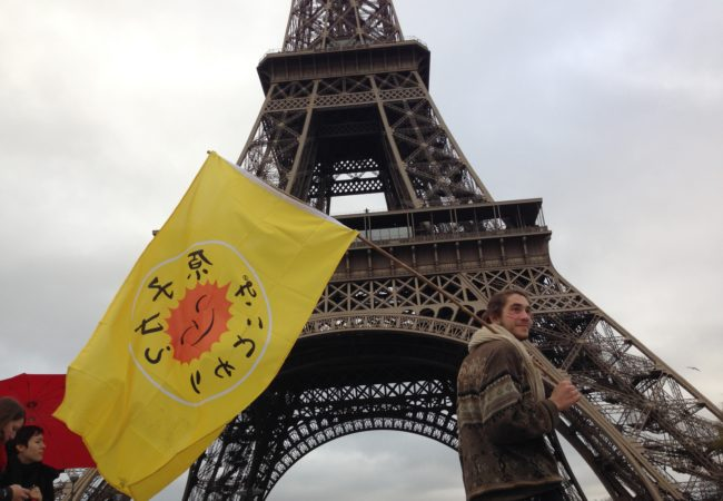 A protestor stood in front of the Eiffel Tower during COP21 in Paris, where 195 countries made climate history, adopting an ambitious and unprecedented international plan to limit global warming to below 2 degrees. (Carlos Felipe Pardo/Flickr)
