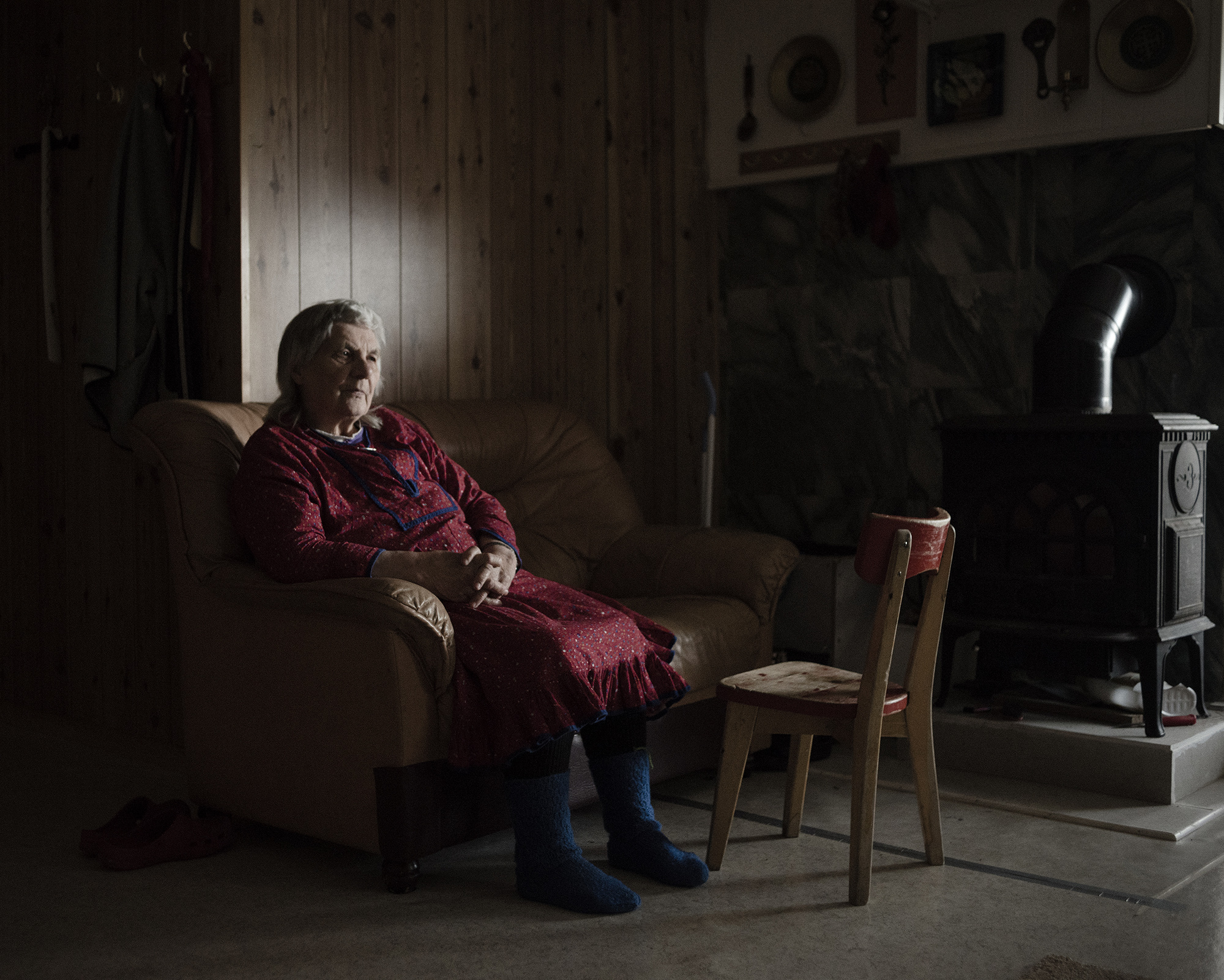 """Marit Sara, 84, from Kautokeino, Norway, has been working as a reindeer herder all her life. The winters today bring new challenges that make it difficult to preserve the semi-nomadic way of life. The ice layers that now form beneath snow make it difficult for the reindeer to reach lichen – their primary food source – so herders must feed them. This type of ice previously only formed during bad years, but it has now become a yearly problem.  Marit Sara says that in her younger days, the river would freeze as clear as glass during wintertime, and she would use fallen reindeer antlers to slide across the ice on her knees. """"That's different now. The ice doesn't get clear anymore."""" (Camilla Andersen/GroundTruth)"""