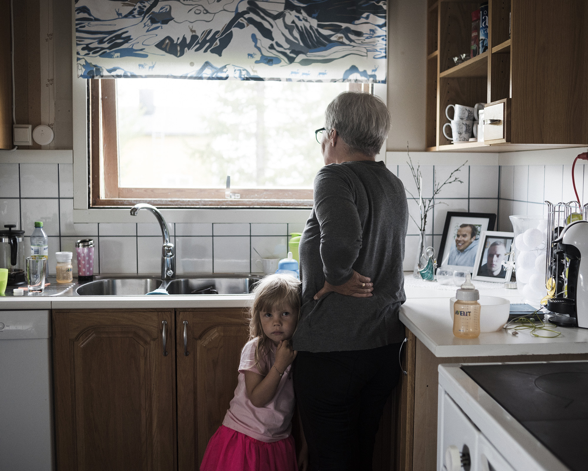 "Randi Marainen and her granddaughter in the kitchen of their home in Nedre Soppero, Sweden.  Randi speaks openly about the taboo topic of seeking mental health services after her sons committed suicide. ""It's very important that we are 100 percent open with everything that happened,"" she said.  (Camilla Andersen/GroundTruth)"
