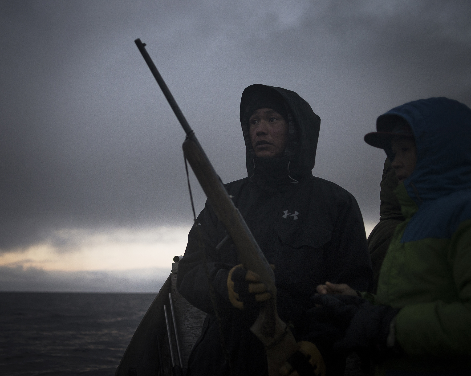 """Nanasi Illauq, 26, and Markoosi Illauq, 15, scan the water for seals. Nanasi has lost two of his older brothers to suicide. The family says there were no warning signs. Traditionally, people seek guidance and help from well-respected elders when they feel lost or depressed. Today the community organization Ilisaqsivik also offers many forms of mental health services. Nanasi says hunting is one of the few things that makes him feel better. He caught his first seal when he was 12. """"I was the proudest boy in the world."""" He says, explaining that the hunting tradition gives him peace because it allows him """"to be alone, where there's nobody around to make me mad or make me depressed."""" (Camilla Andersen/GroundTruth)"""