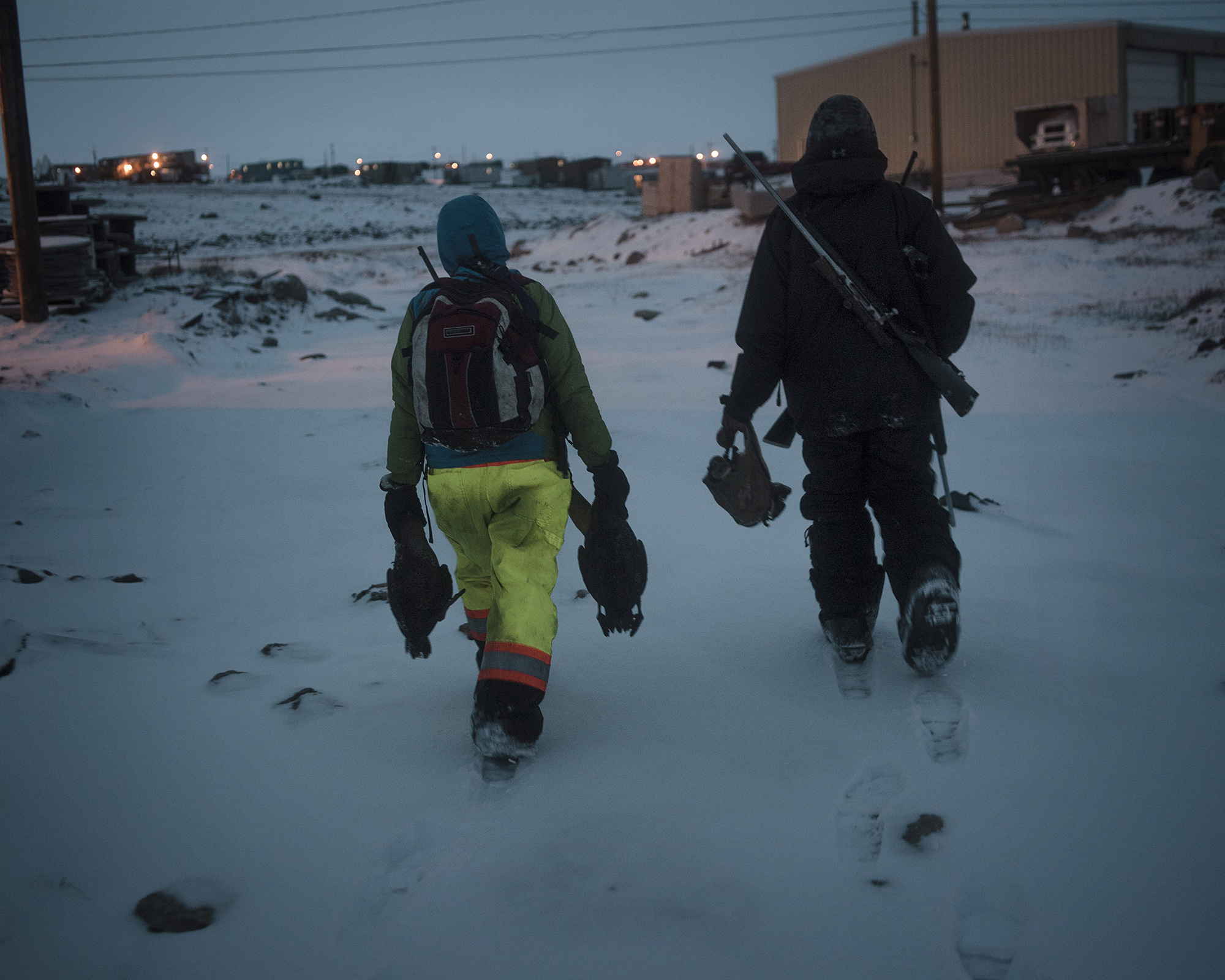 Markoosi and Nanasi Illauq walk home with their catch. The Nunavut Bureau of Statistics reports that the price of food in Clyde River is three times higher than the national average. And hunting is less reliable, because of loud modern boats and shifting water patterns due to climate change. Many hunters return home after a long day with an empty gas tank and no game to show for it. As a result of this, half of the population does not get enough food each day. (Camilla Andersen/GroundTruth)
