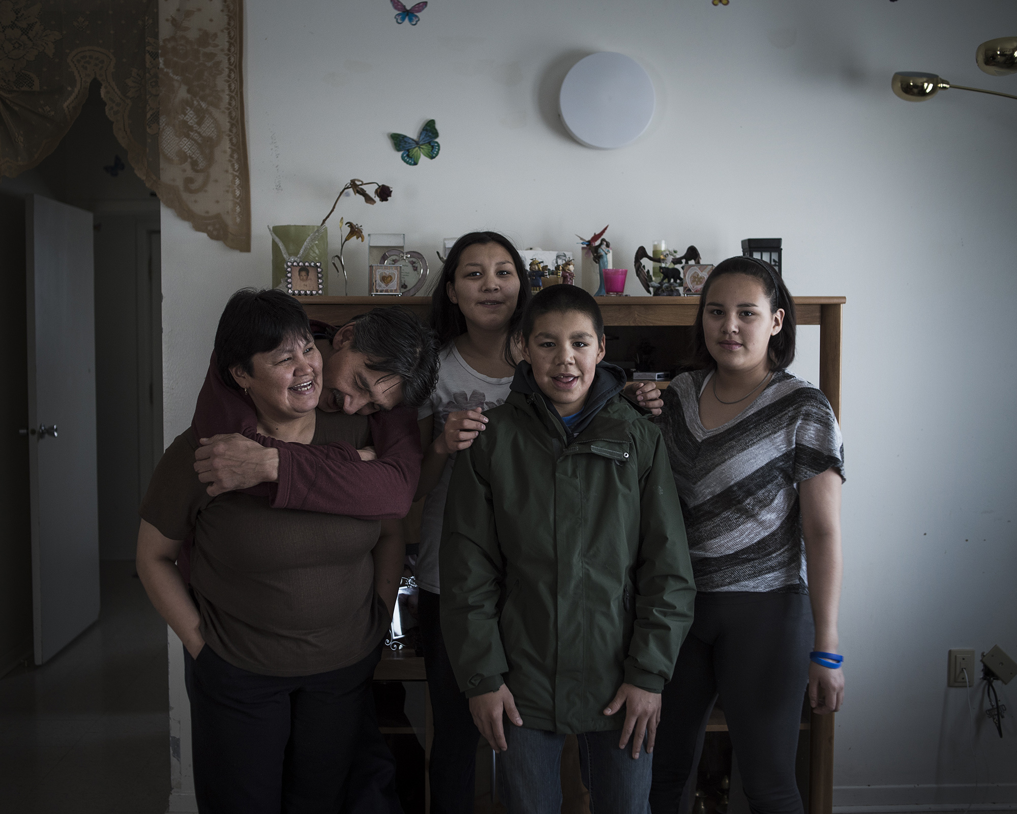 """The Natanine family. Christine Natanine (left) runs Ilisaqsivik, which offers counseling and mental health care to Inuit residents. Her husband, Jerry, (second from left) is the former mayor of Clyde River, and one of the most vocal proponents of protecting indigenous ways of life in the community. """"A lot of the problems we have would be solved if we could be on the land."""" Jerry says. (Camilla Andersen/GroundTruth)"""