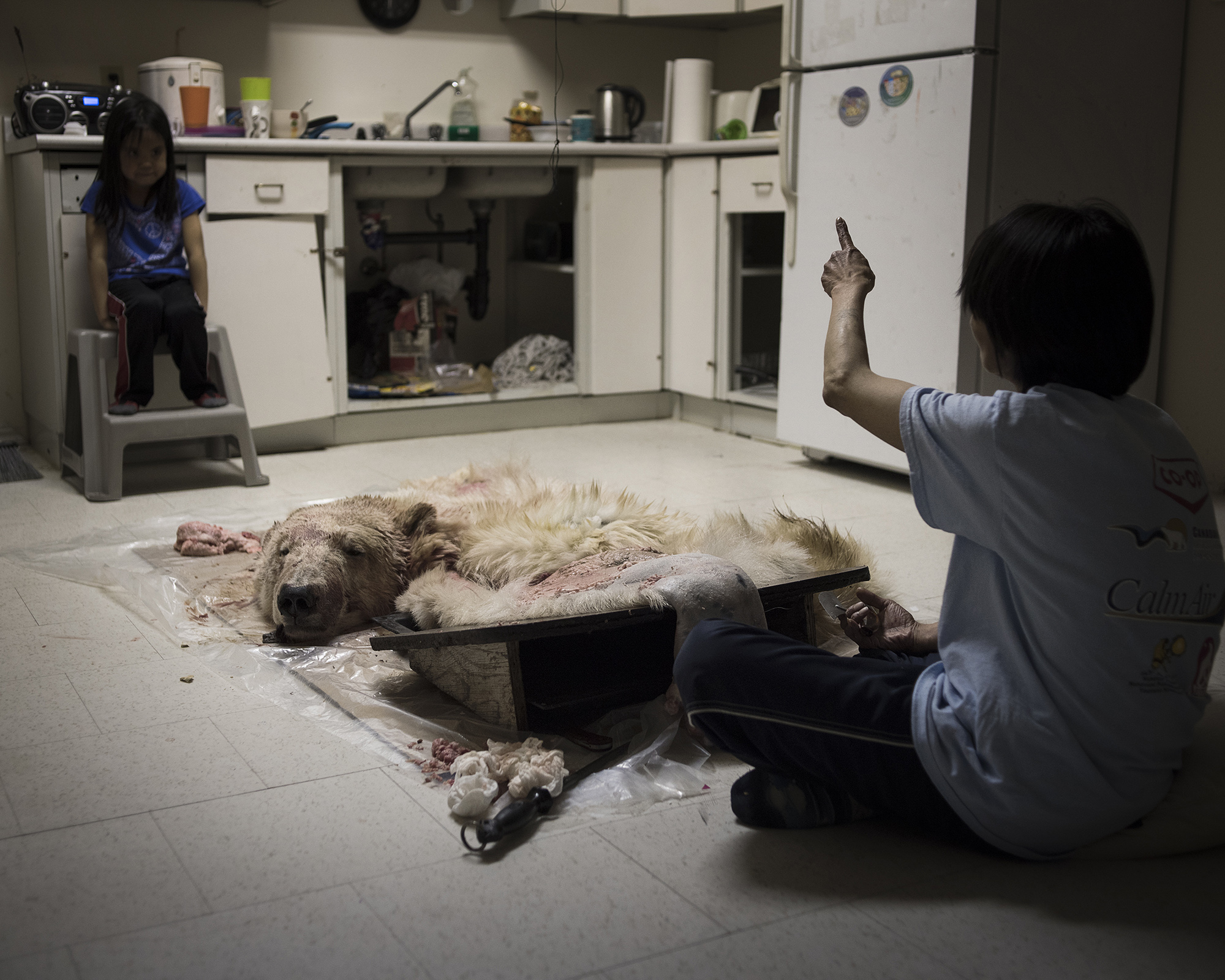 A girl watches her grandmother remove the fat from the polar bear pelt. One pelt can easily go for $10,000 if it's in good condition. More than half of the Inuit diet consists of fresh game. However, currents in the water draw trash and pollution from all over the world up to the Arctic, which gets absorbed into marine mammals' meat and fatty tissue. (Camilla Andersen/GroundTruth)