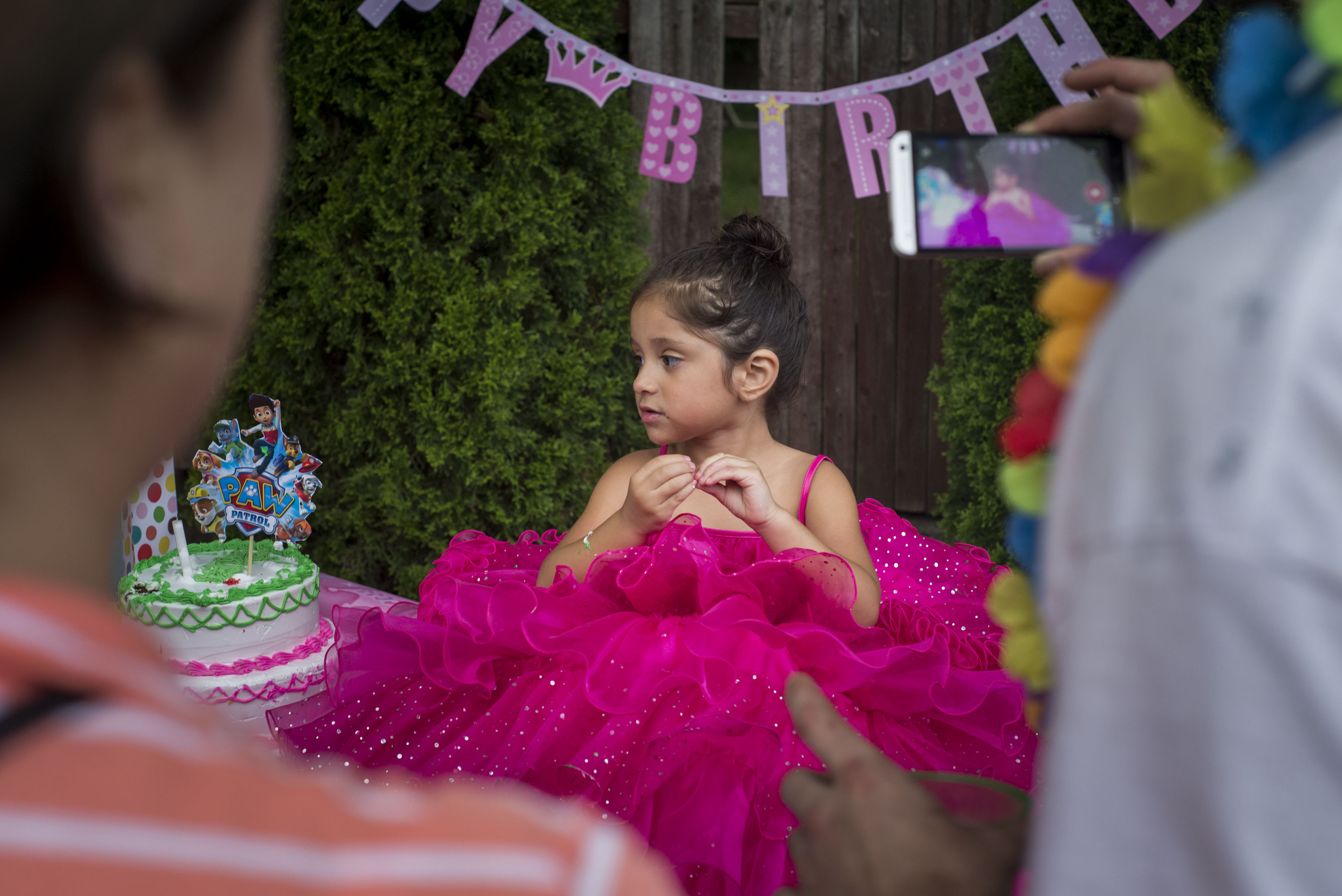 My niece, Rubi Sepulveda, 4, wears a large puffy dress and is posed like a doll for her birthday in Revere, Massachusetts. (Photo by Iaritza Menjivar/GroundTruth)